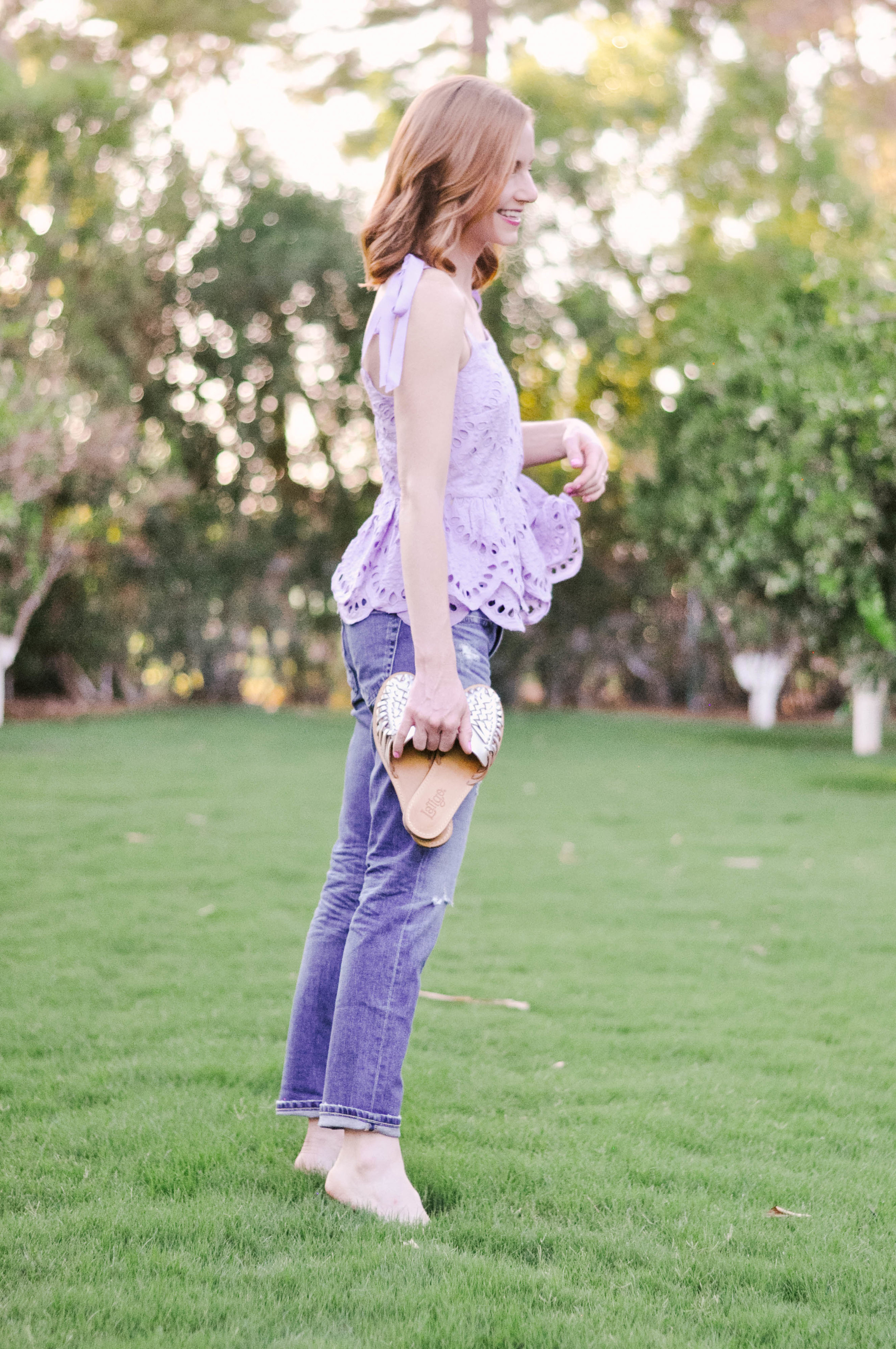Girl with red hair standing in a field in a lavender J.Crew top and AG boyfriend jeans