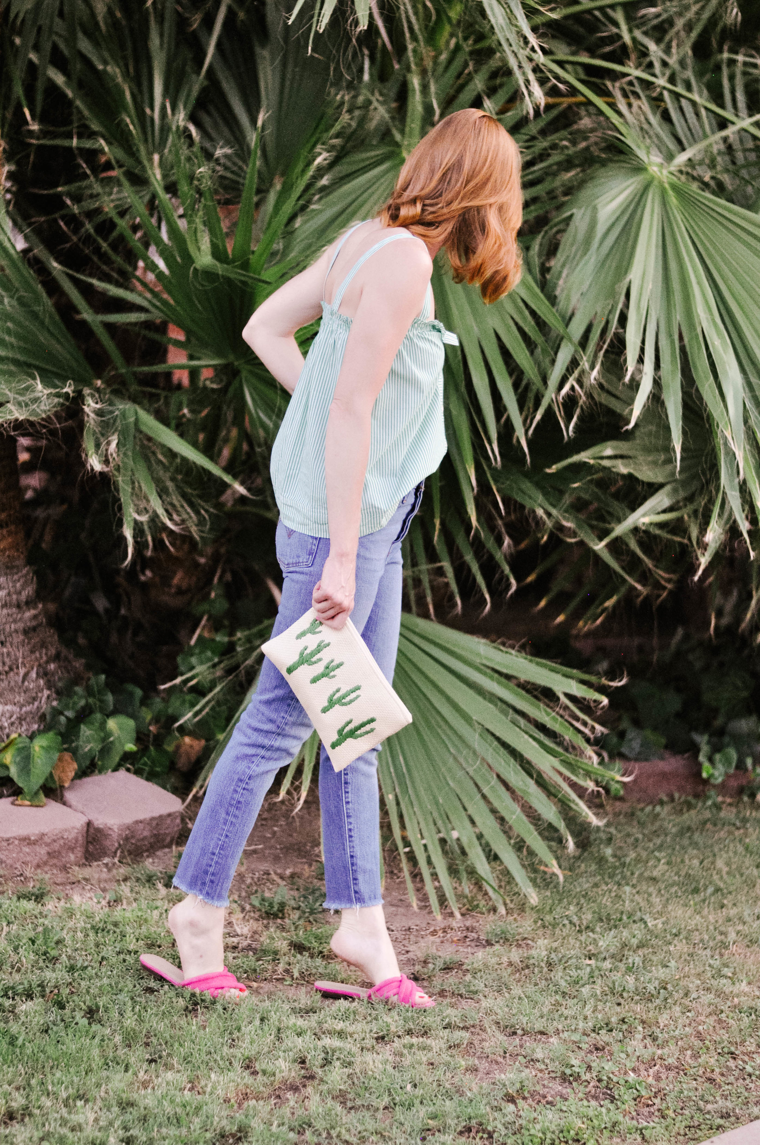 Woman Standing in Front of Palm Tree in a Casual Summer Outfit