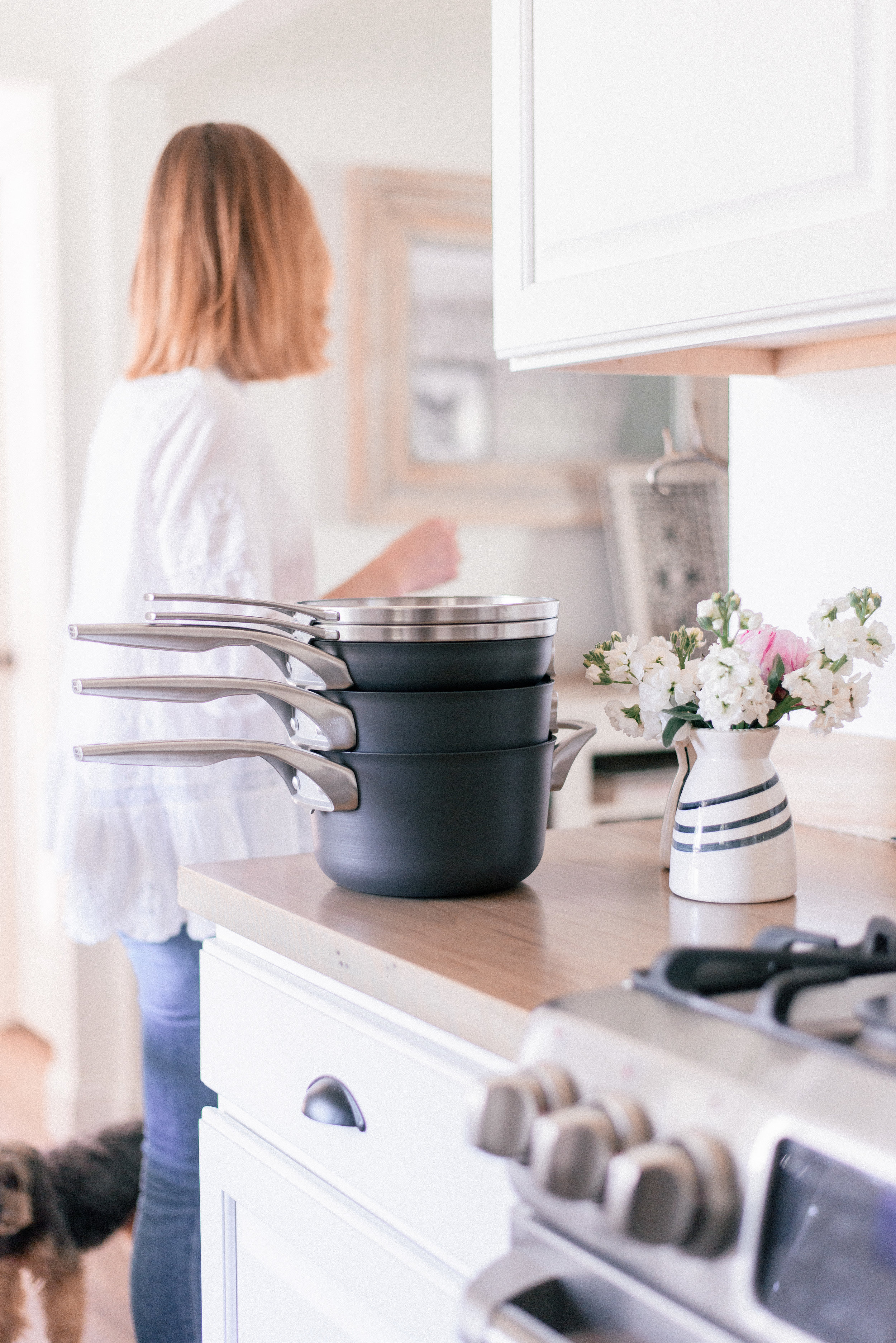 The Best Nonstick Cookware Sets with Calphalon and Bed Bath & Beyond featured by top U.S. Lifestyle blog Love + Specs: image of woman in white shirt next to Calphalon nonstick pans in kitchen
