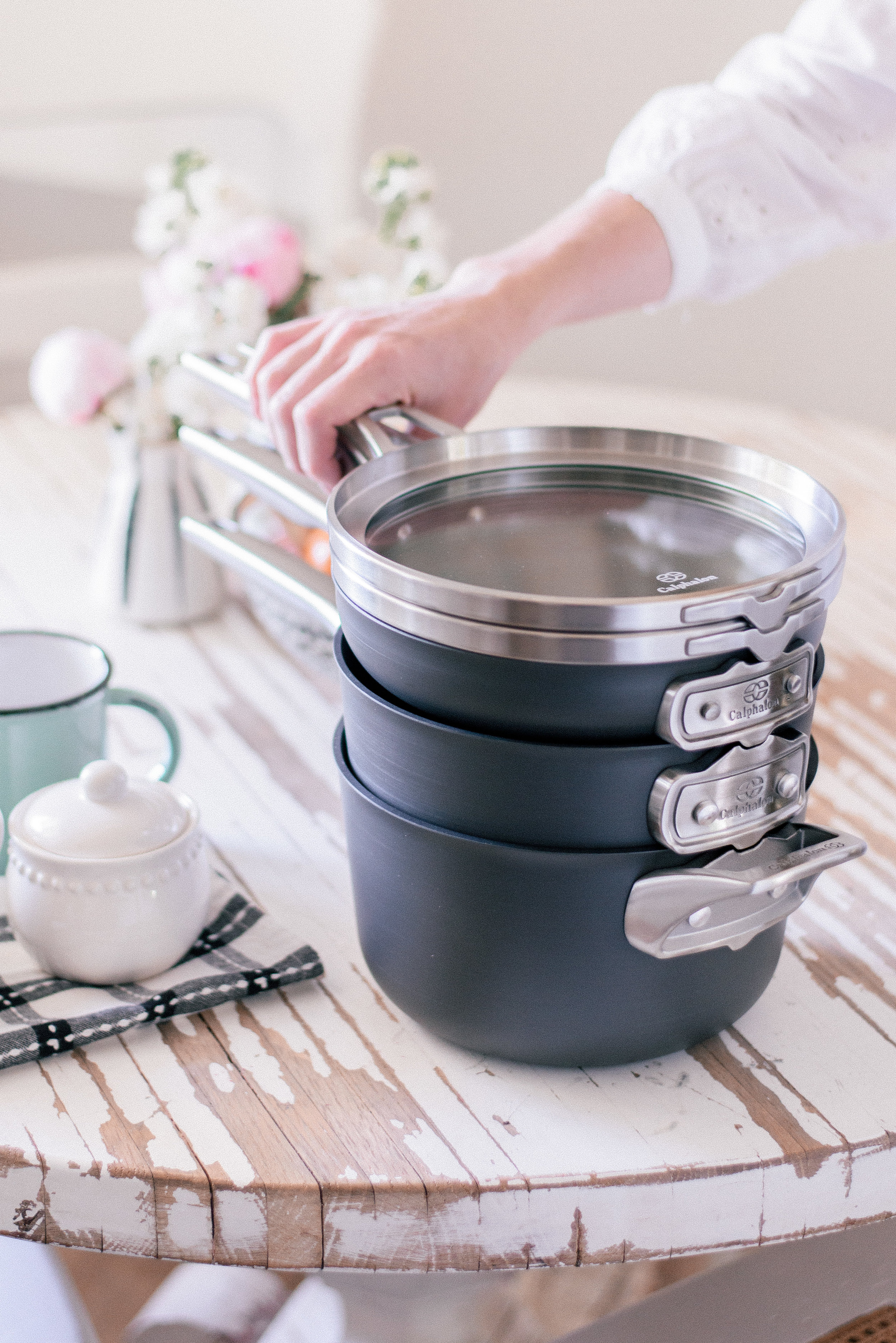 The Best Nonstick Cookware Sets with Calphalon and Bed Bath & Beyond featured by top U.S. Lifestyle blog Love + Specs: image of woman holding Calphalon pans in cottage kitchen stove