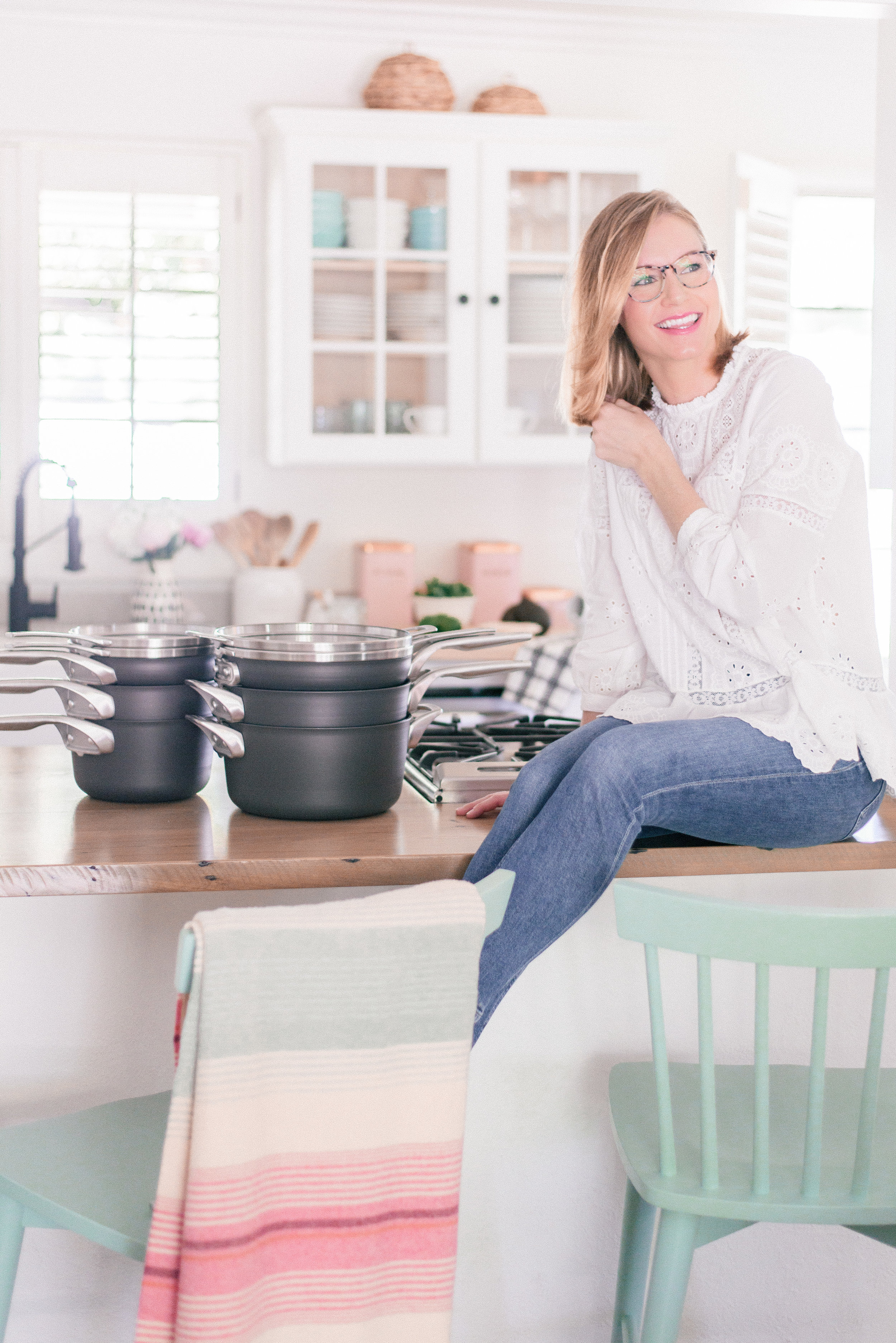 The Best Nonstick Cookware Sets with Calphalon and Bed Bath & Beyond featured by top U.S. Lifestyle blog Love + Specs: image of woman in white shirt sitting next to Calphalon pans in kitchen