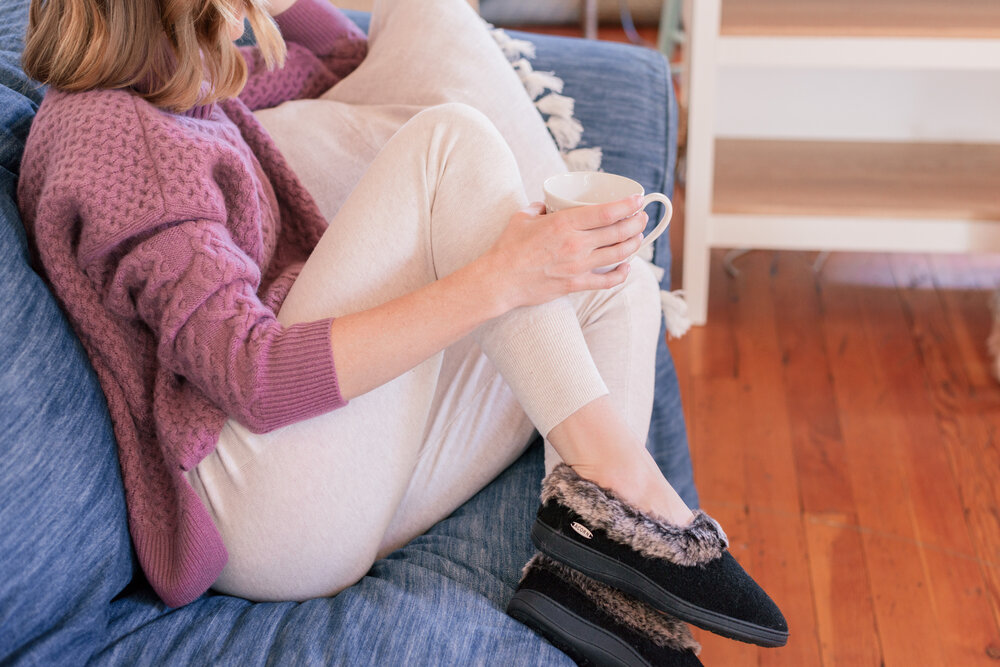 20 fun fall bucket list ideas for couples by top US lifestyle blog, Love + Specs: image of a woman  wearing Acorn slippers at home on the couch