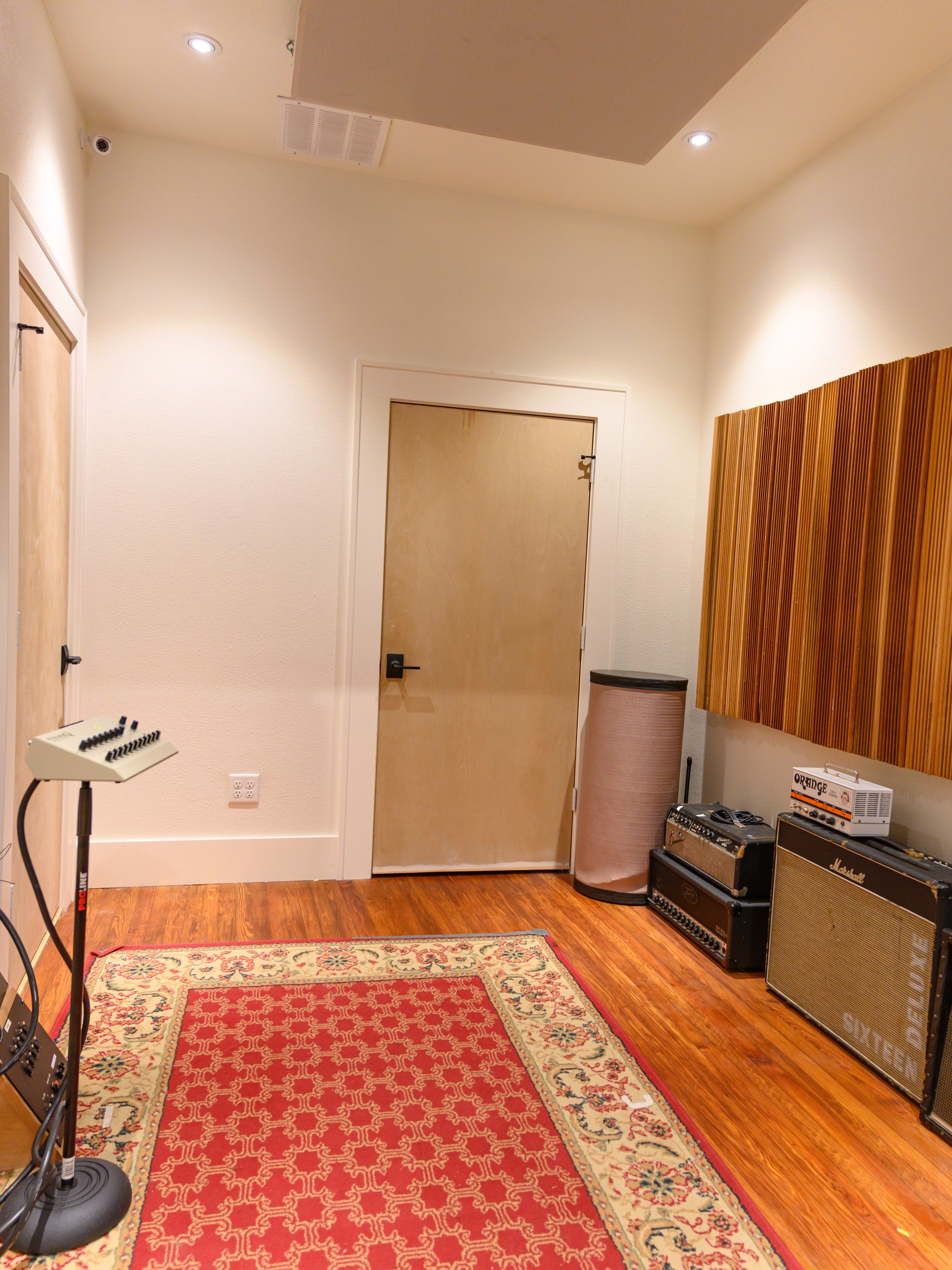 "We have one over sized isolation booth with diffusion and ceiling clouds with sight-lines to the main room. Also two identaical ""amp closets"". All with tie lines for easy access. -"