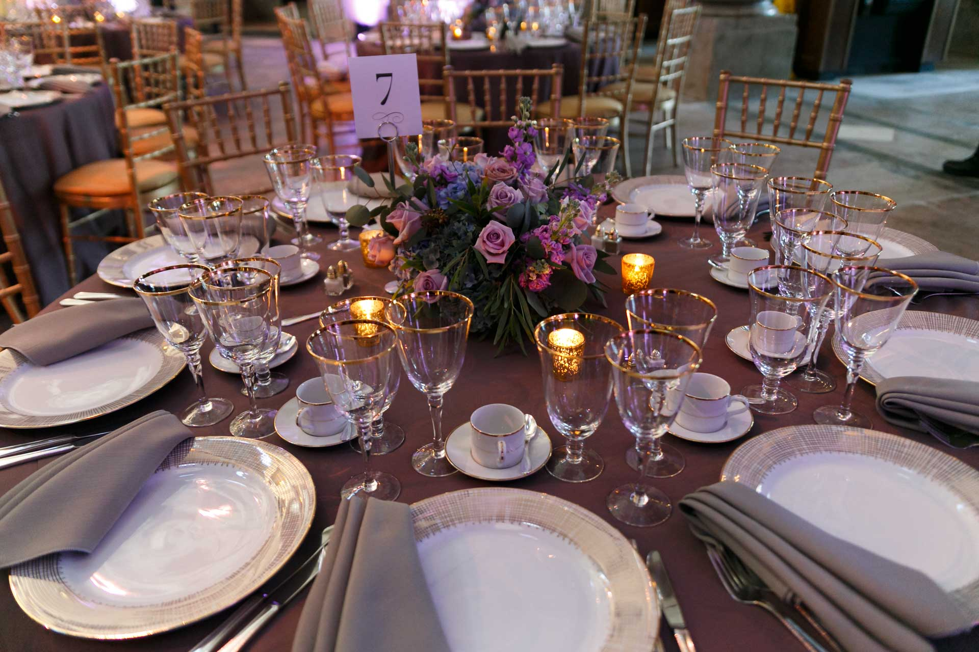 This set up was gorgeous with a perfect plum linen, gold accents and the flowers bringing in the dusty hues of blue, green and lavender. Catering and rentals by  Occasions Caterers