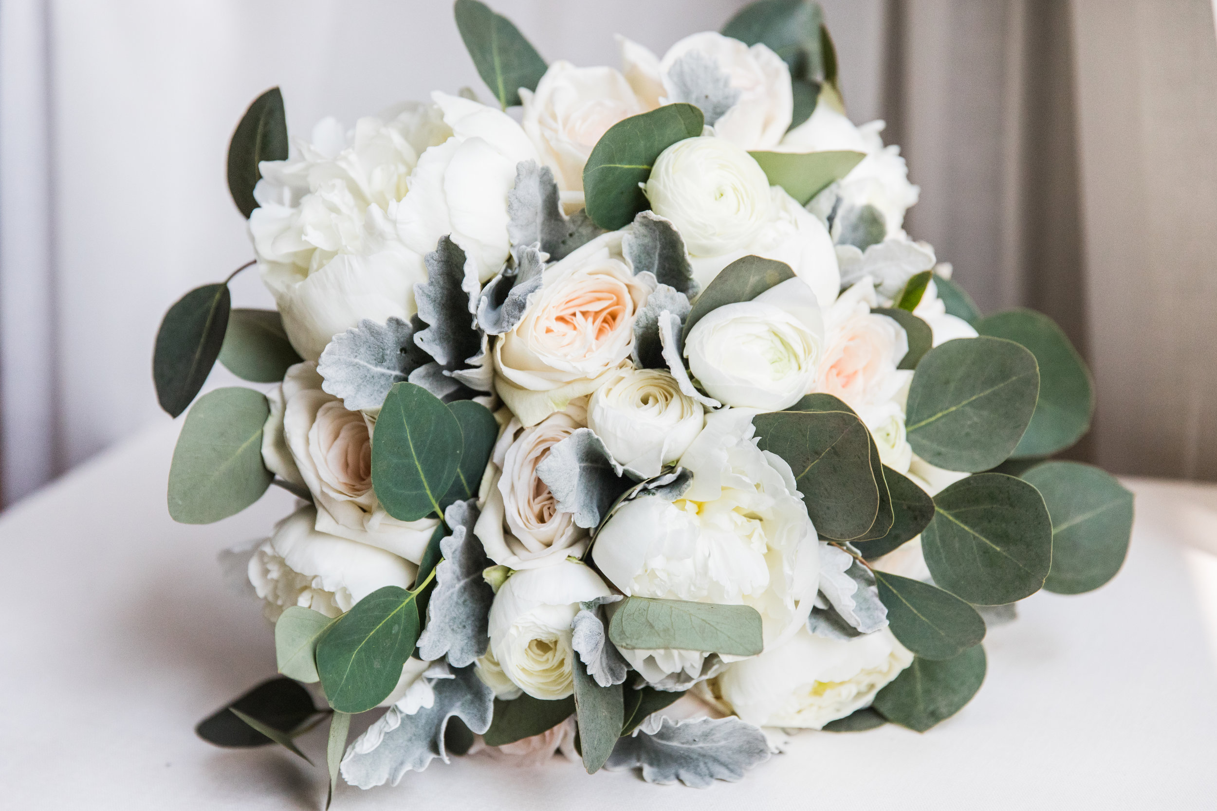 Gorgeous bridal bouquet of peonies, ranunculus, roses, eucalyptus and dusty miller