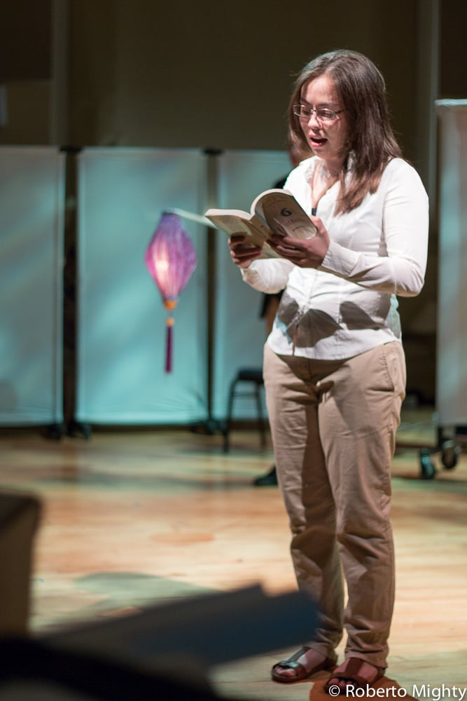 Vietnamese-American student Trinh Nguyen (Helen Swanson) reads a poem by the Vietnamese poet Y Nhi. The play is structured around a fictional study tour of Vietnam by a group of contemporary U.S. college students. As part of their preparation for the trip, the students are given an assignment to interview people about their experiences with the Vietnam War draft. (Photo Credit: Roberto Mighty).