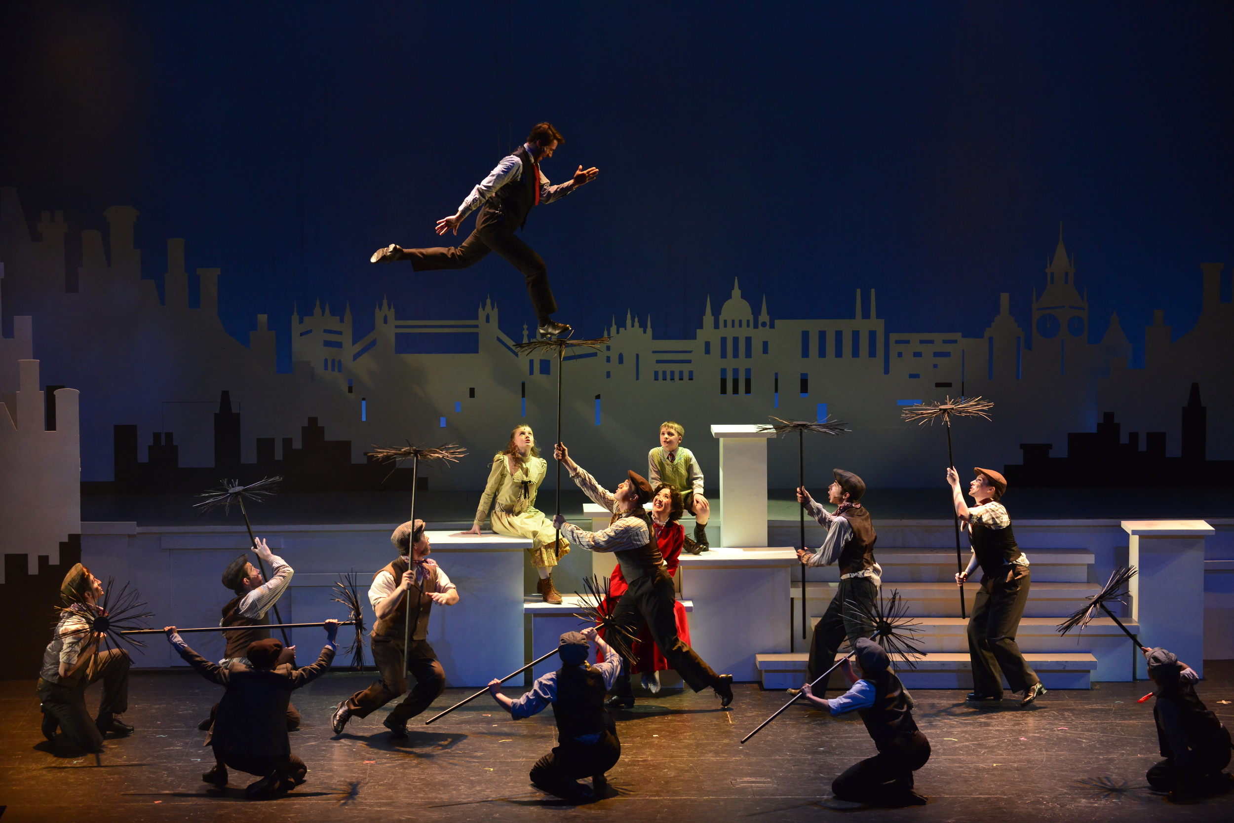 Bert (Dan Reardon*) flies above the other chimney sweeps in Wheelock Family Theatre's  Mary Poppins  (Photo Credit: Gary Ng) (* Denotes a Member of Actors' Equity Association).