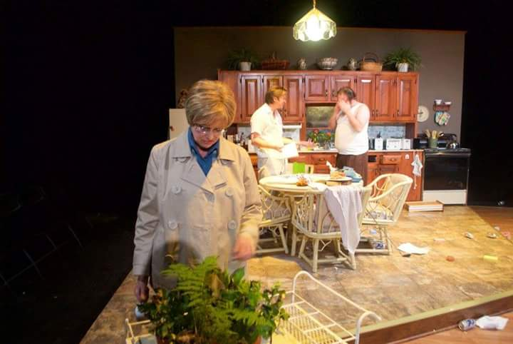 Mom (Nancy Curran Willis) looks at her dying plant as Austin (Michael Carr) and Lee (Gordon Ellis) fight in the background in  The Umbrella 's  True West  (Photo Credit: Meghan Donnelly).