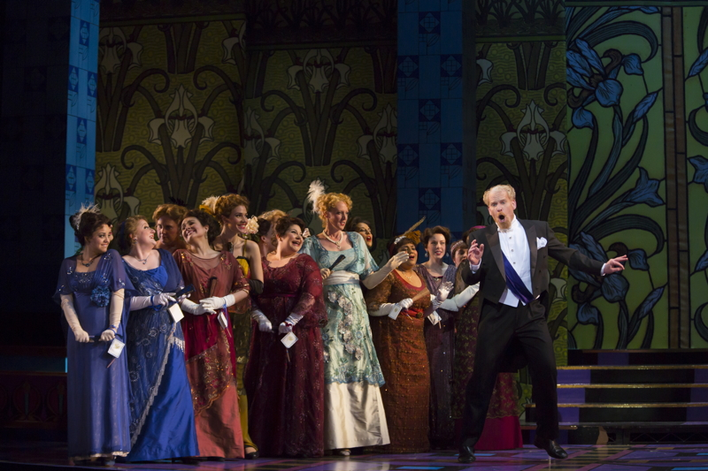 Count Danilo ( ROGER HONEYWELL) sings as surrounded by the ensemble in Boston Lyric Opera's new production of  The Merry Widow  (Photo Credit: T. Charles Erickson).