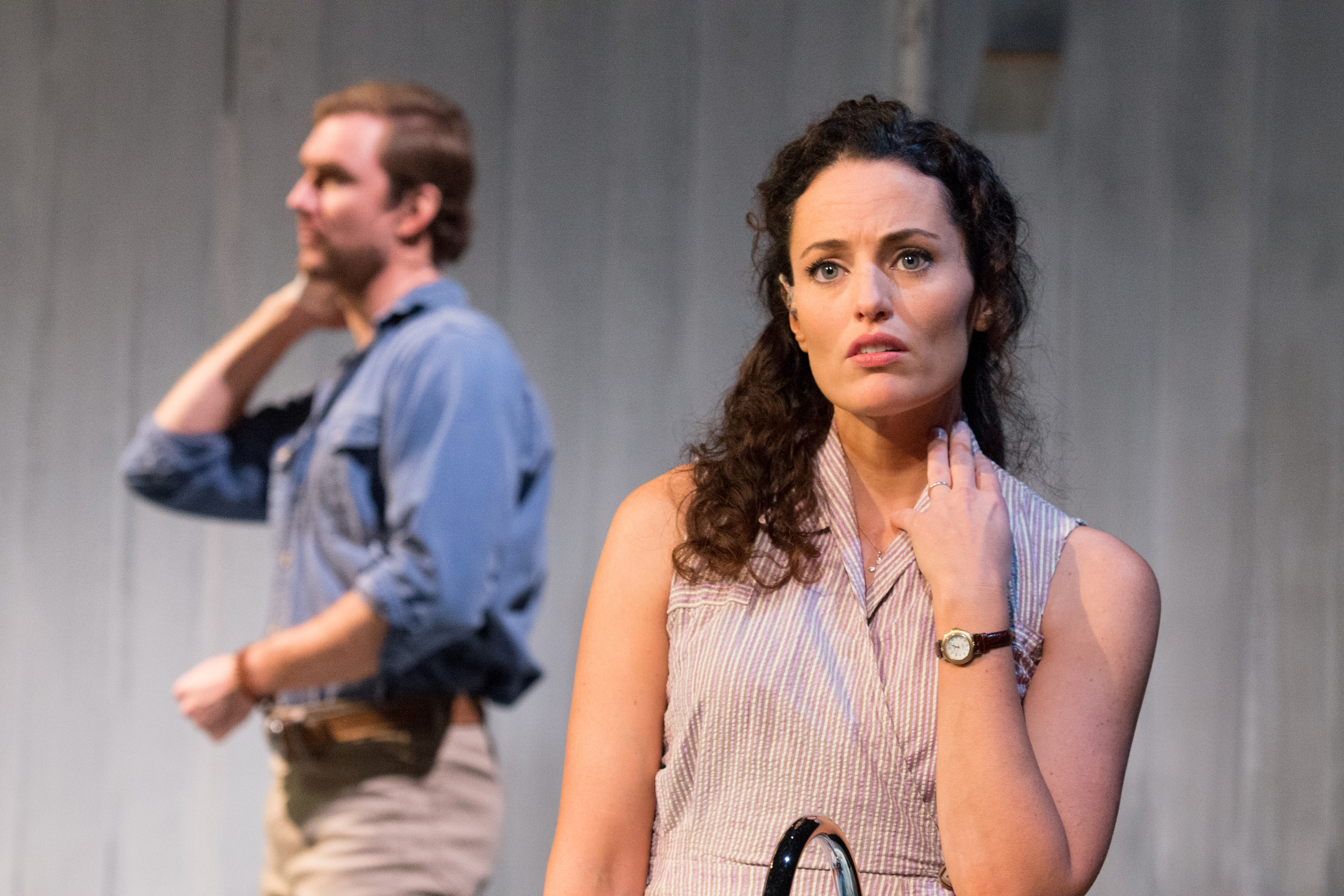 Francesca ( Jennifer Ellis ) watches Robert ( Christiaan Smith ) clean up in  The Bridges of madison county at SpeakEasy Stage Company. Photo by Glenn Perry.