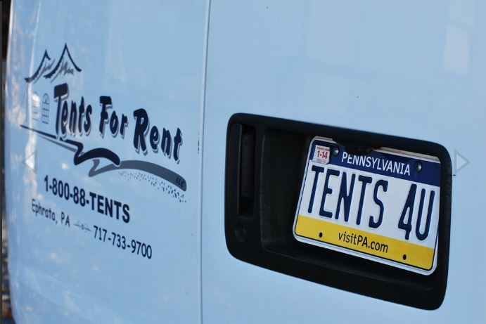 """Tents for rent van with a license plate reading """"Tents 4 U"""""""