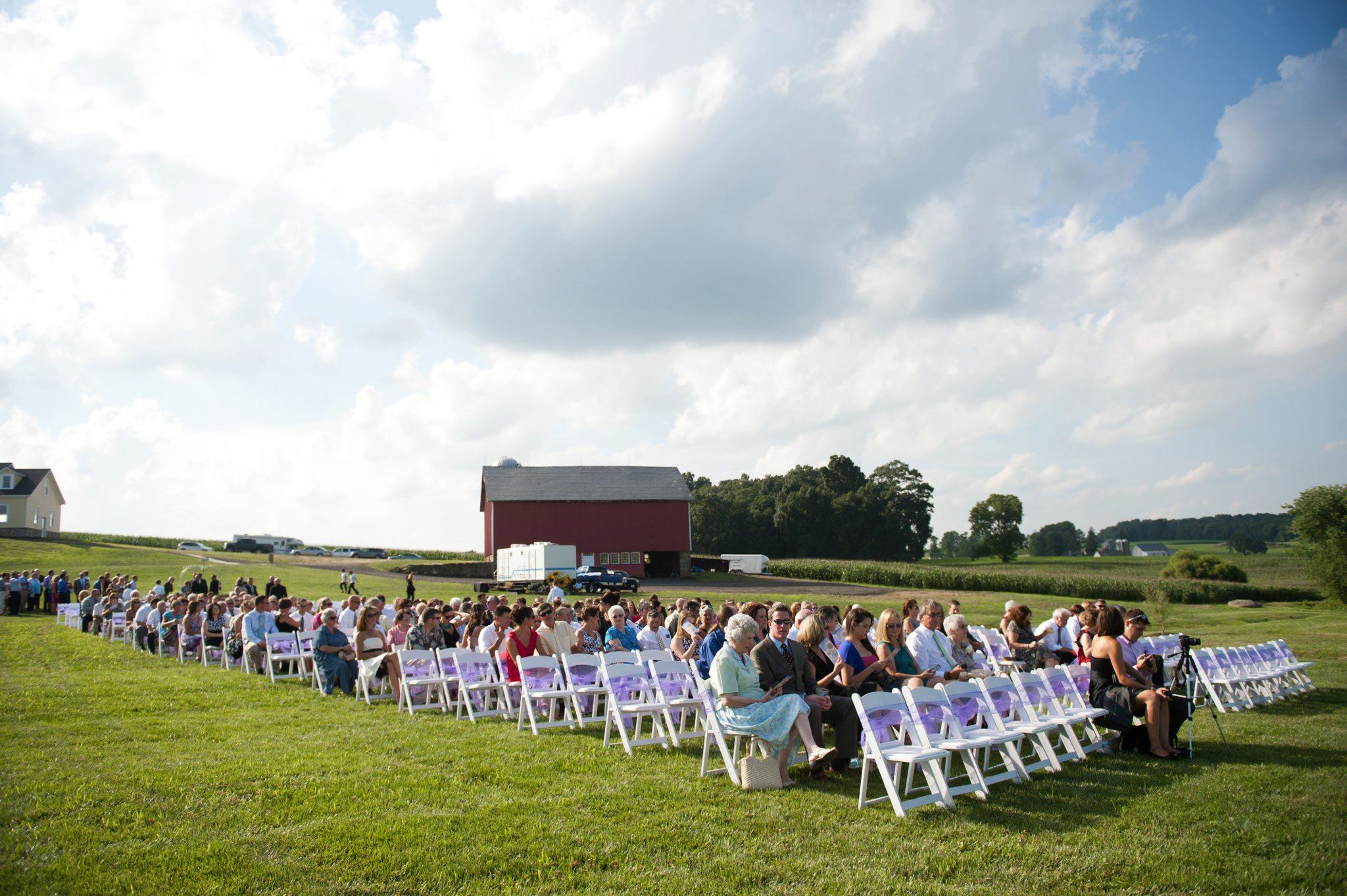 Wedding ceremony with white padded garden chairs
