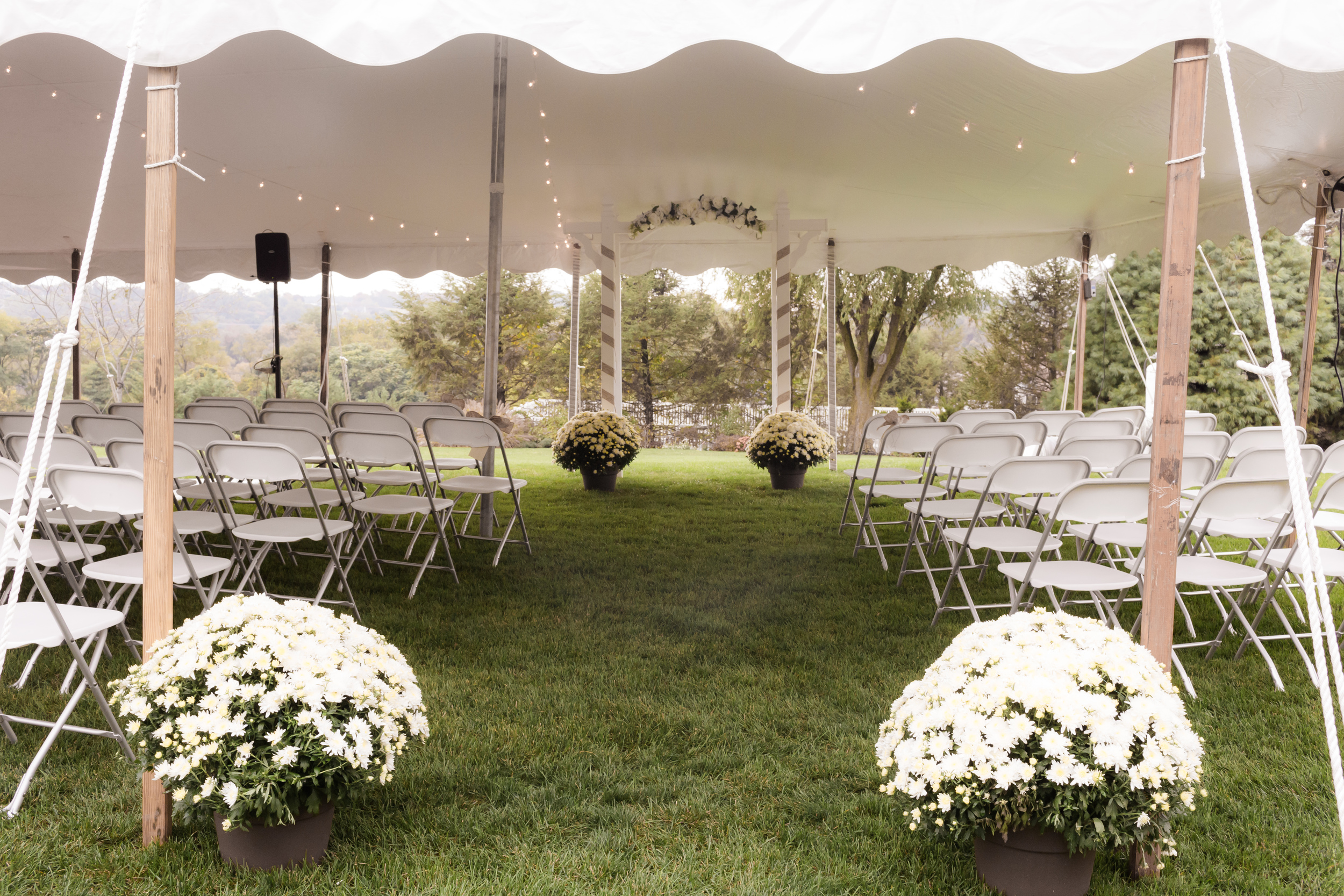 White wedding tent with white folding chairs