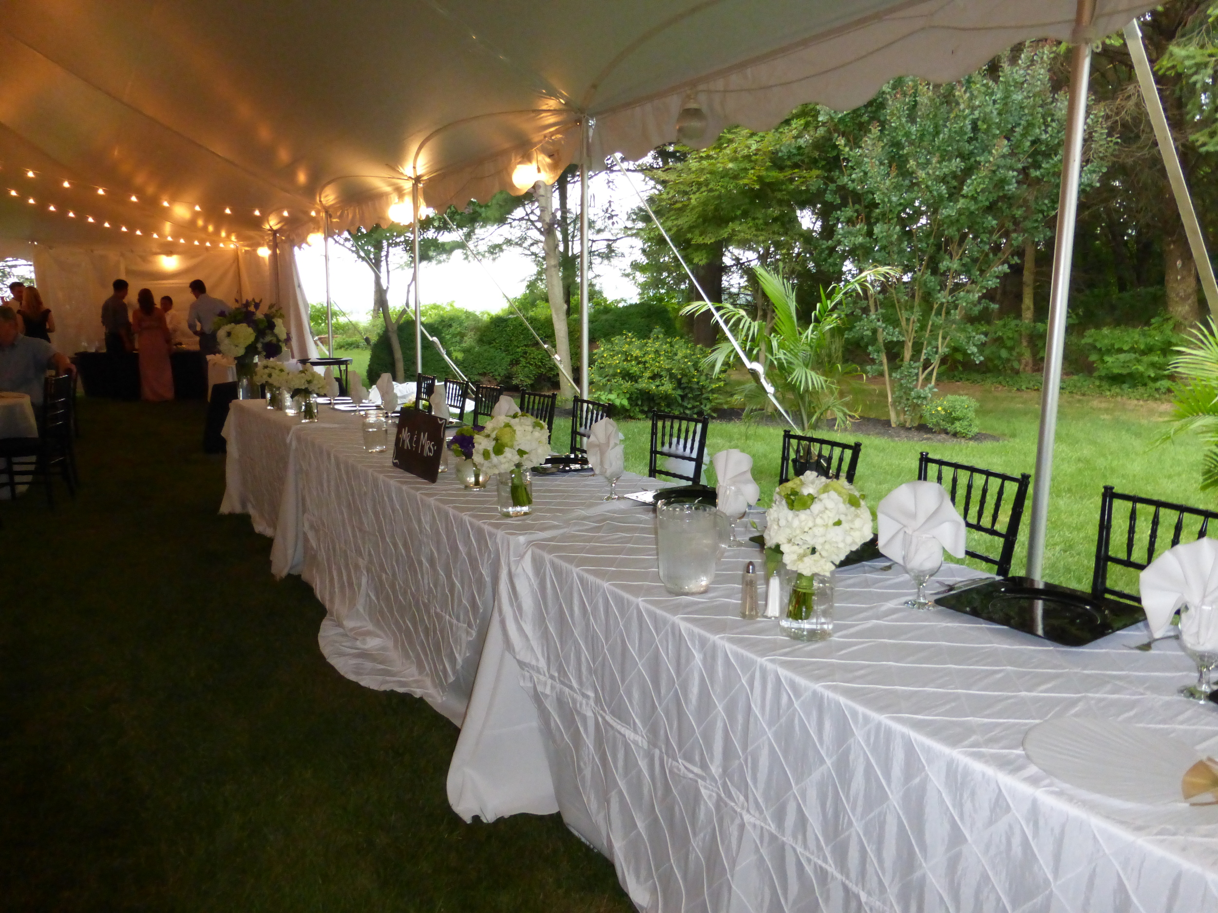 White wedding tent with cafe lights and globe lights