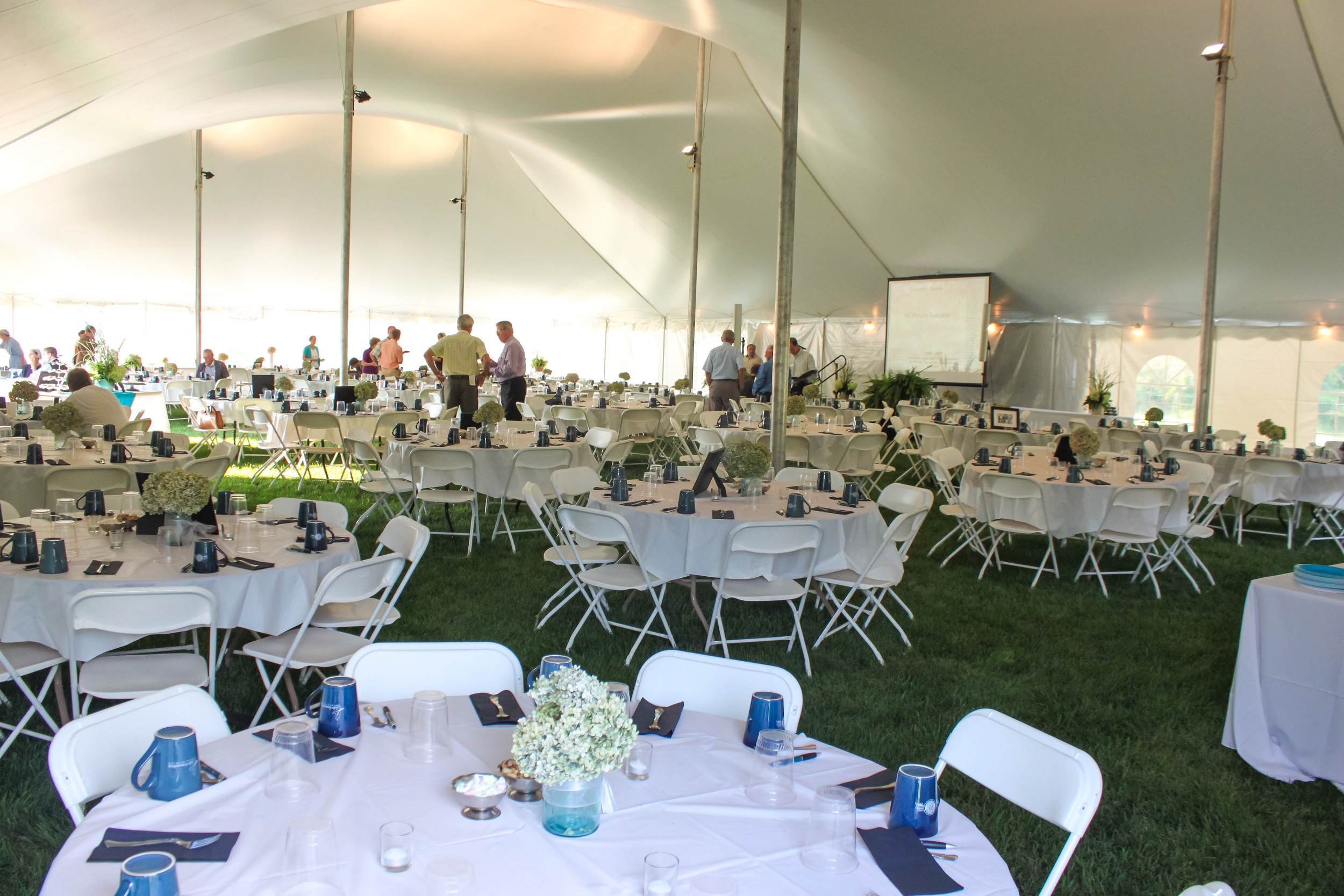 "White folding chairs and 60"" round tables"