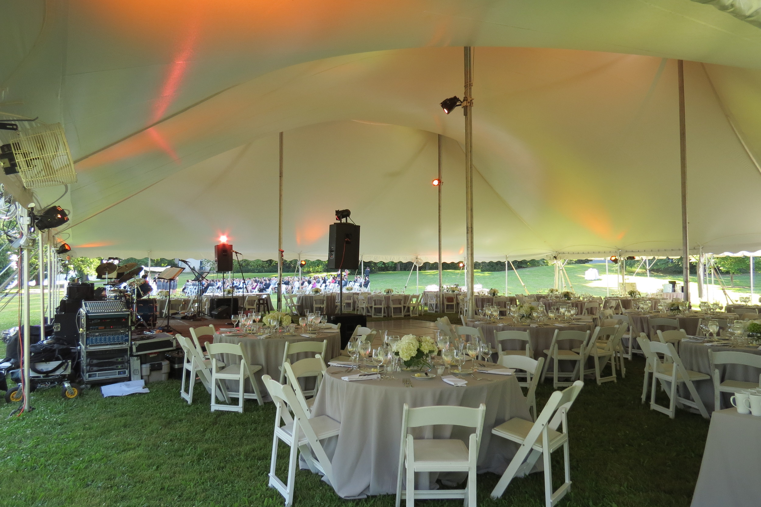 "White padded chairs and 60"" round tables"