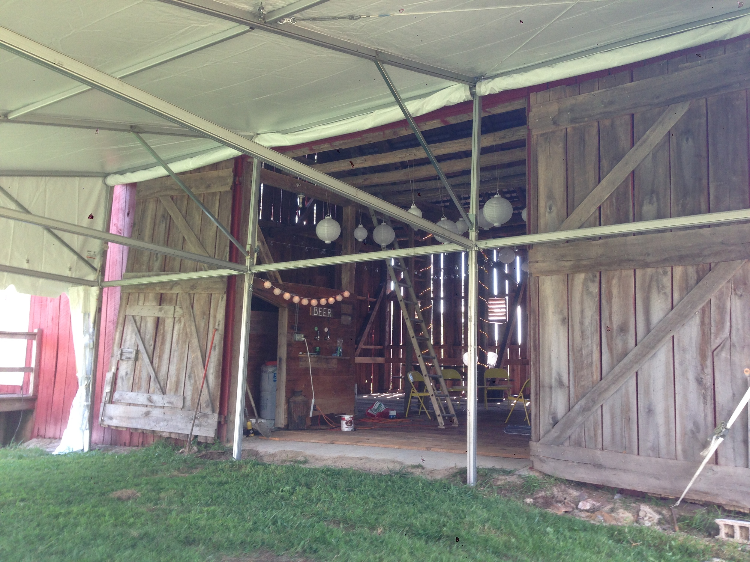 Single slope pavilion tent next to a barn
