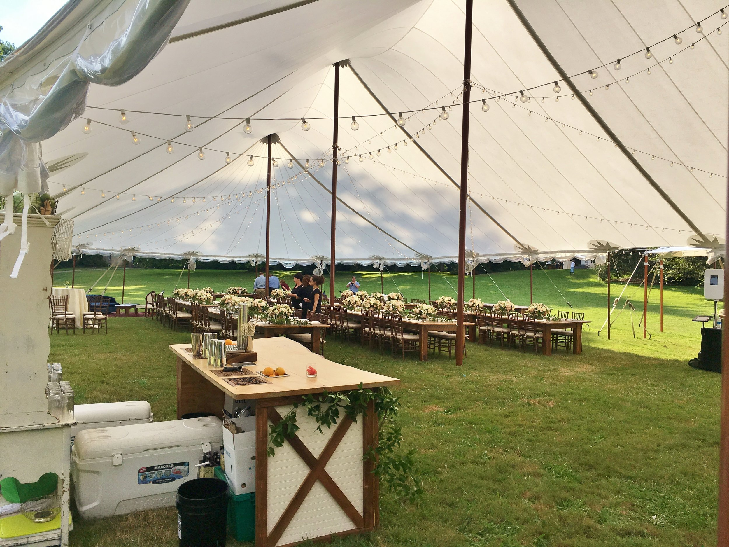 Sailcloth wedding tent with cafe lights and faux wooden poles