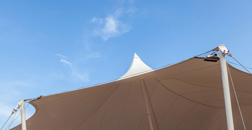 Looking up at the top of white tent against clear blue sky backg