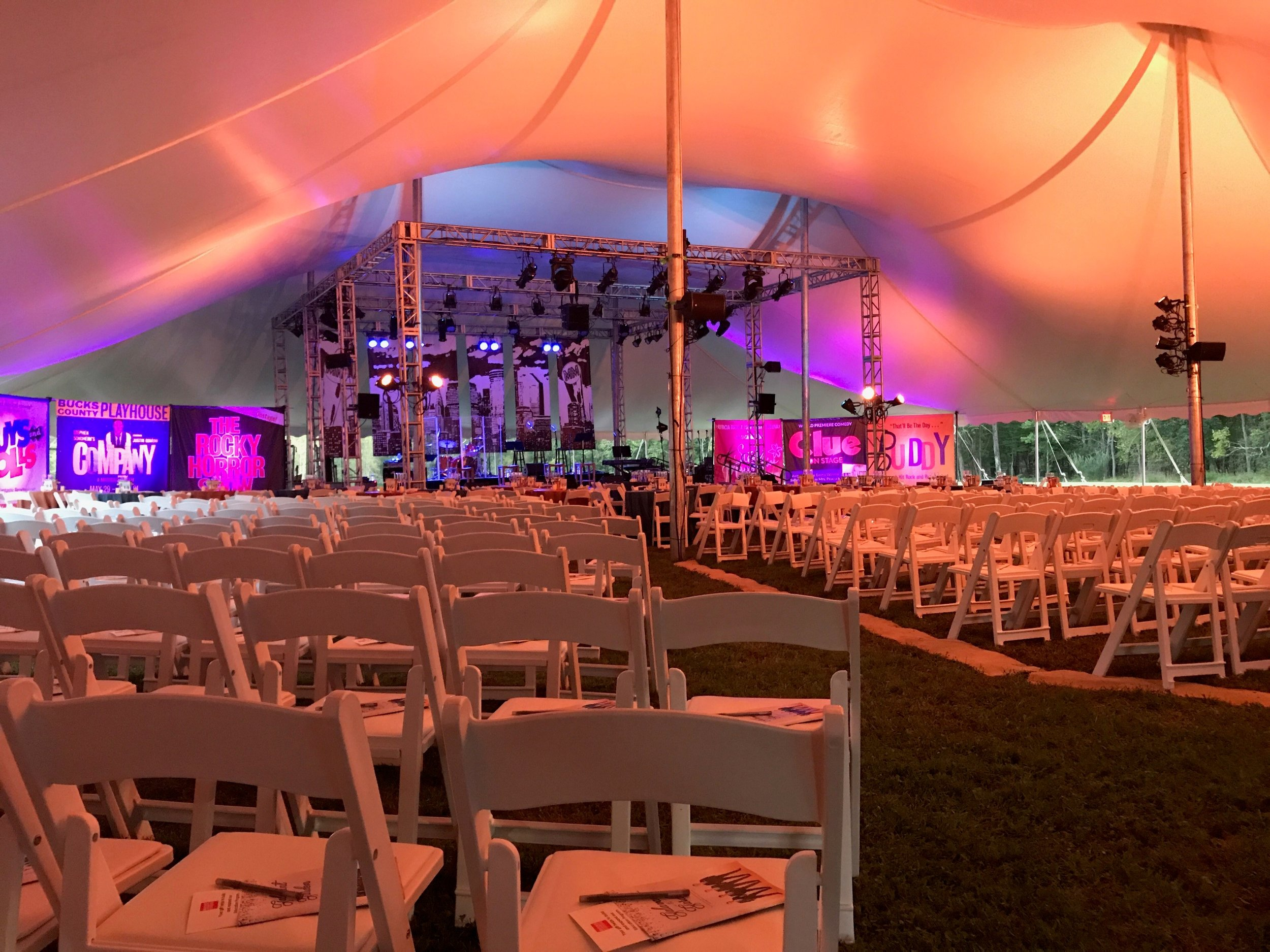 White padded chairs for tent wedding ceremony