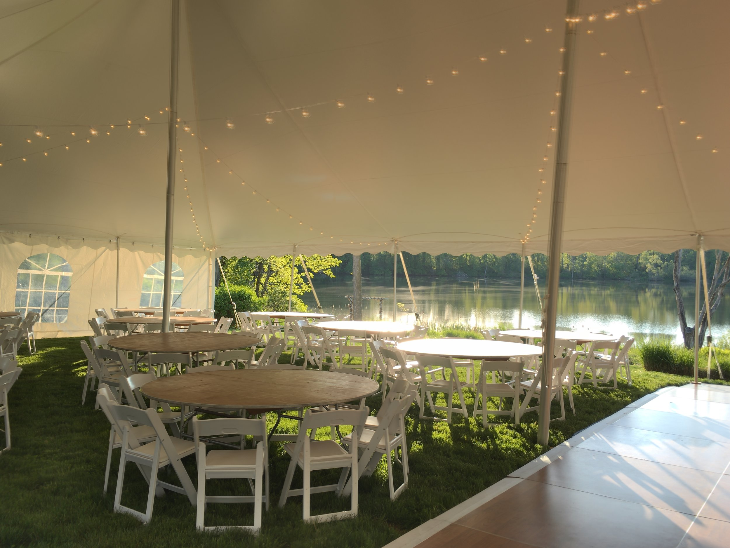 cafe lighting, dance floors, white padded chairs and round tables for your tent wedding