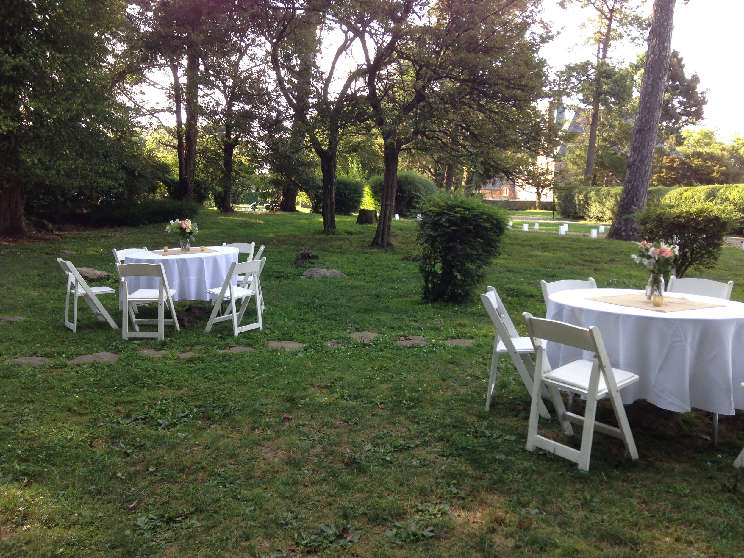 Round tables and white padded folding garden chairs for your outdoor reception