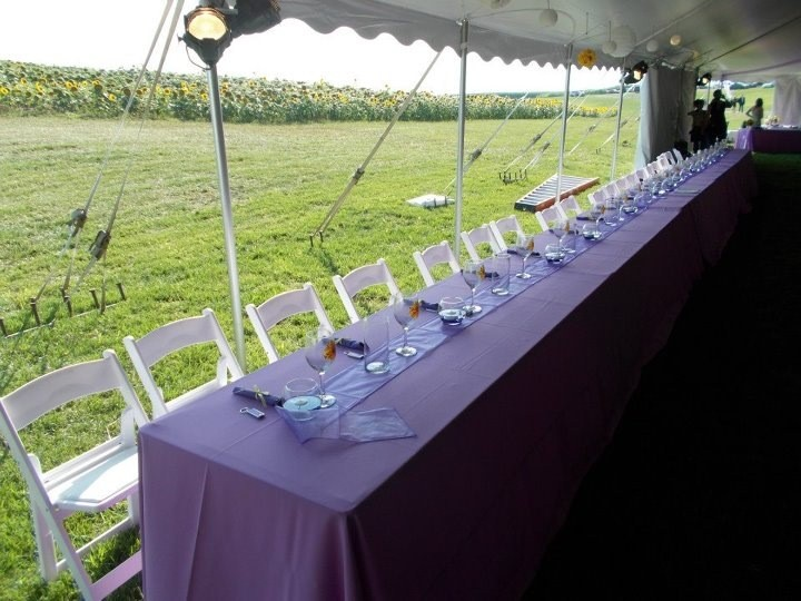 Long tables and white padding folding chairs for your wedding reception under the tent