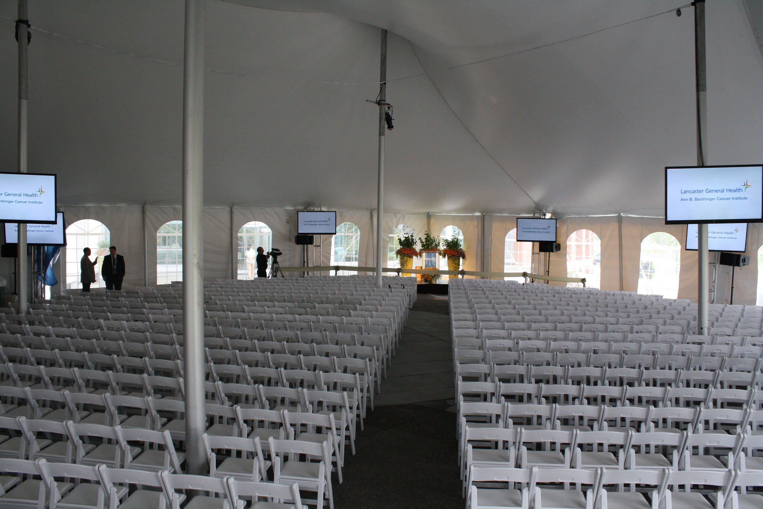Large amounts of white padded folding garden chairs for your tent event