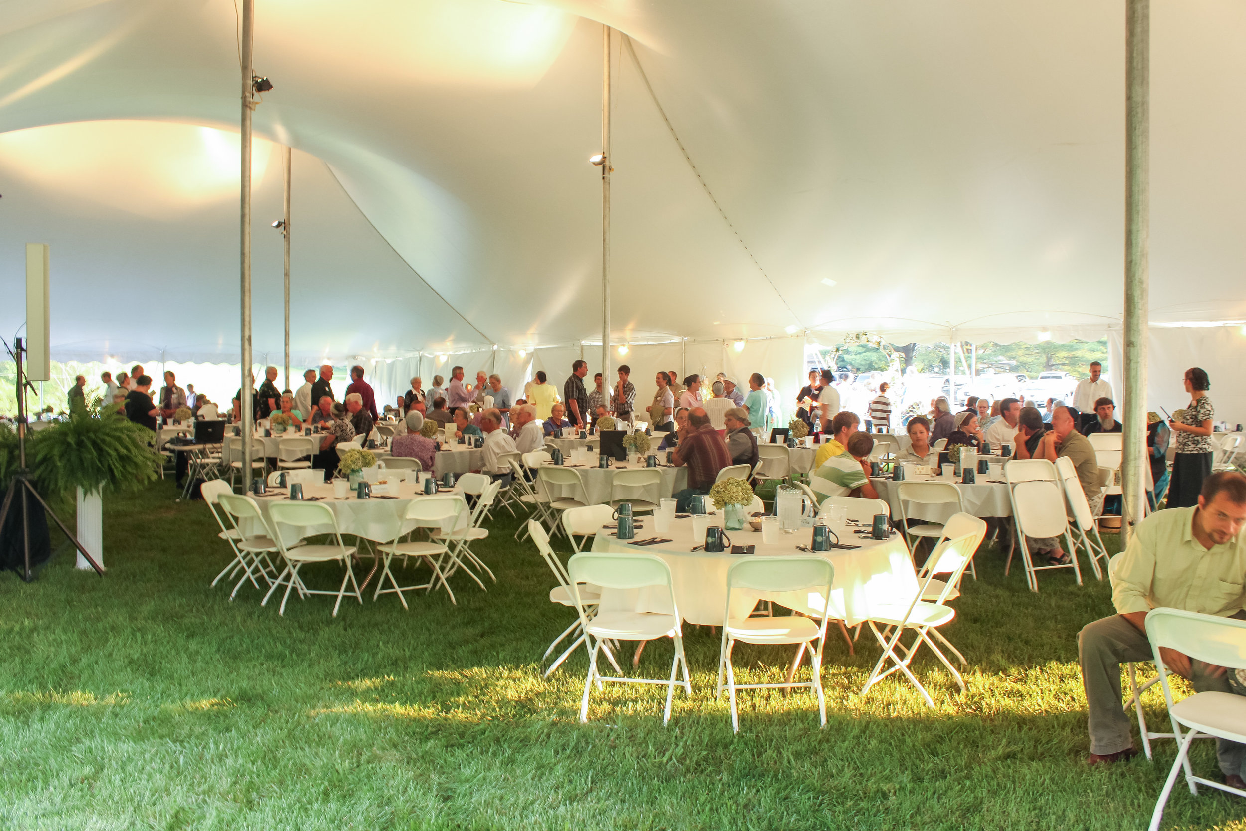 White folding chairs and round tables for your tent wedding reception