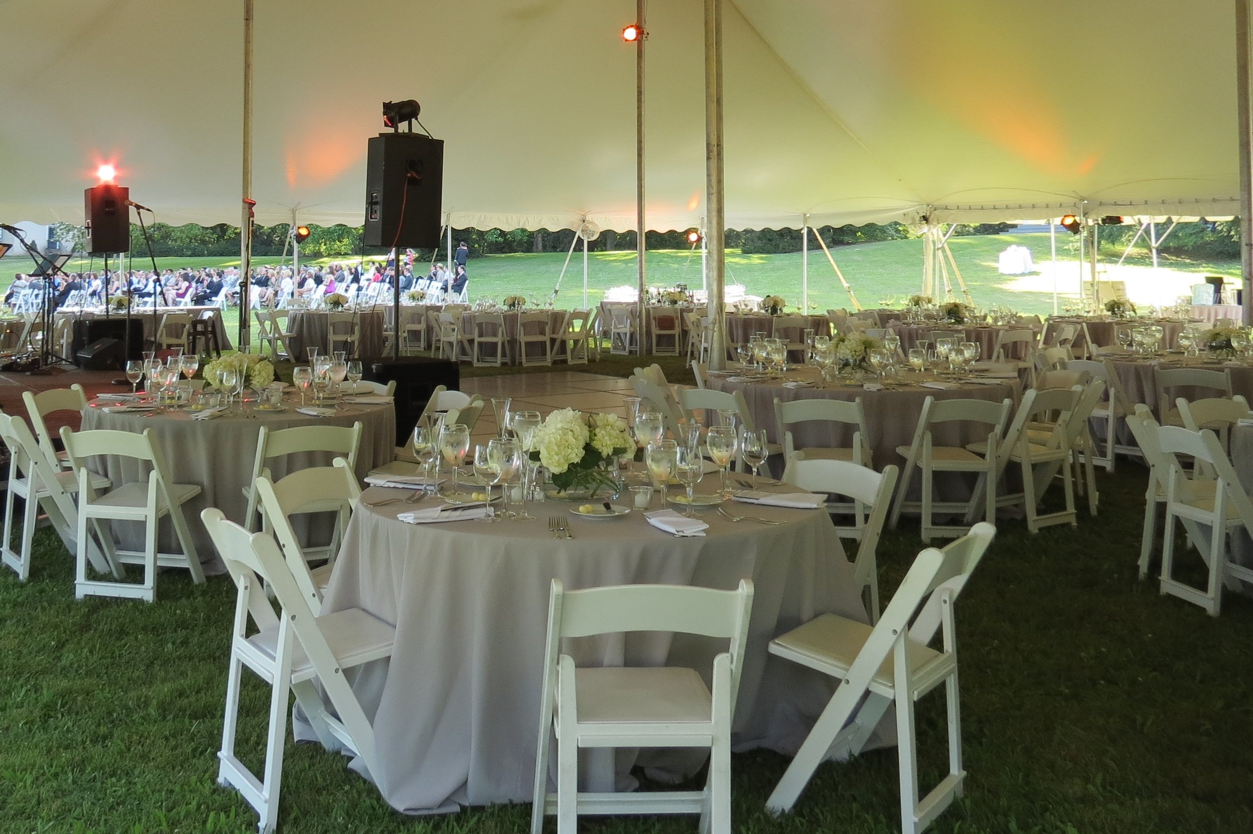Round tables and white padded folding garden chairs for your tent reception