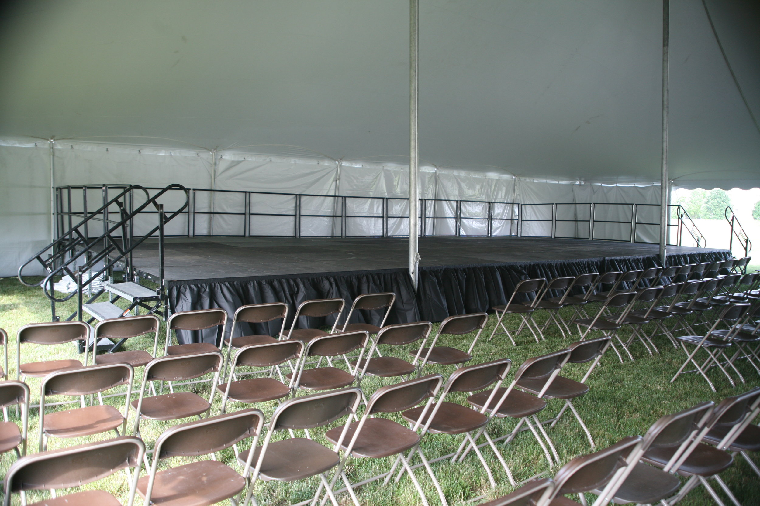 Brown folding chairs and a stage to rent for your tent event