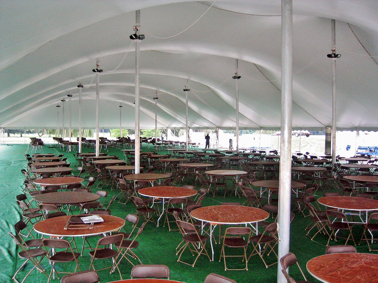 Brown chairs, round tables and flooring to rent for your tent event