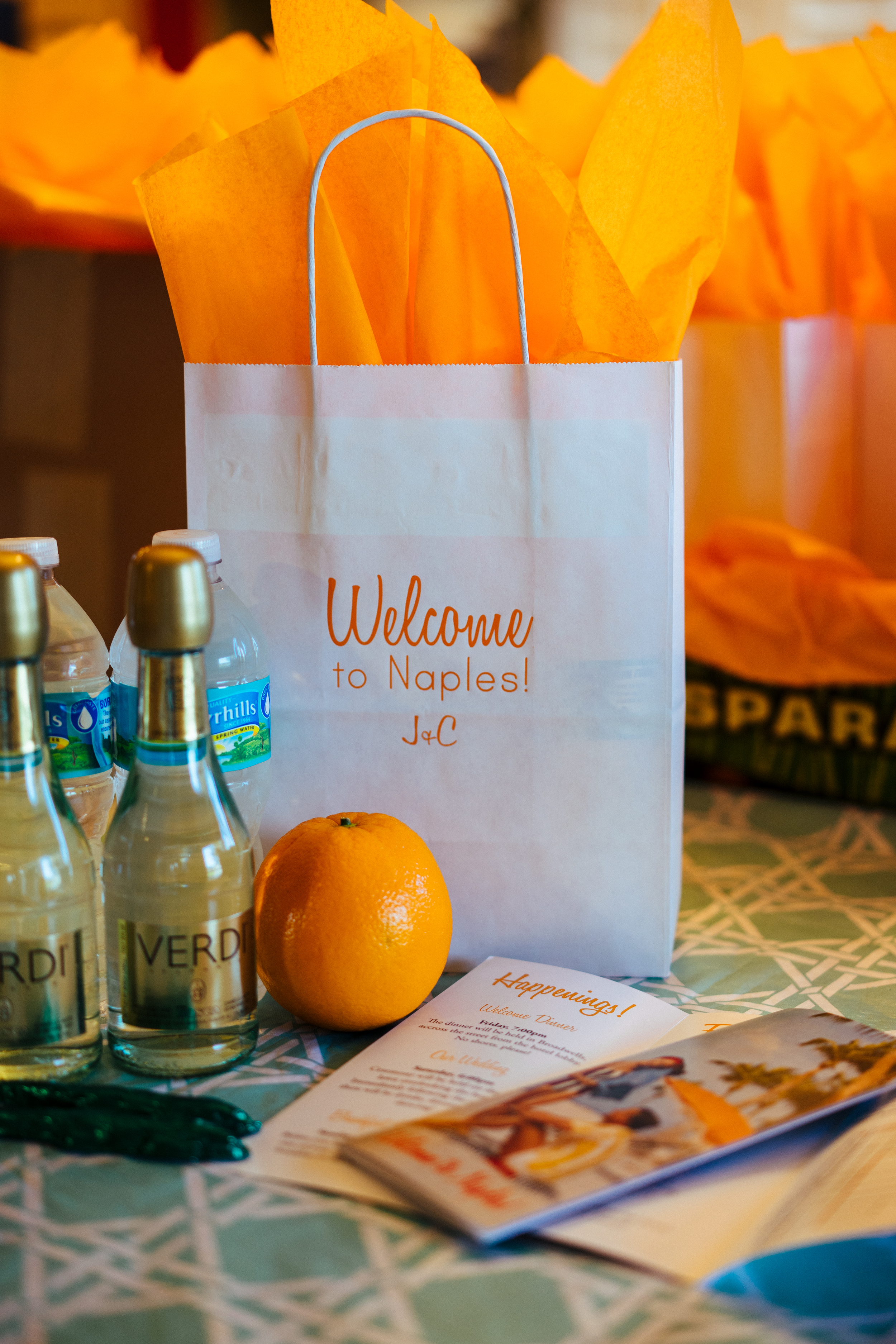 A glimpse at our welcome bags. We wanted these to be very Floridian (and scream vacation), so we included oranges, little chocolate alligators, and an itinerary for the wedding which we designed to look like a retro tourism pamphlet. ...oh and champagne, just 'cuz.