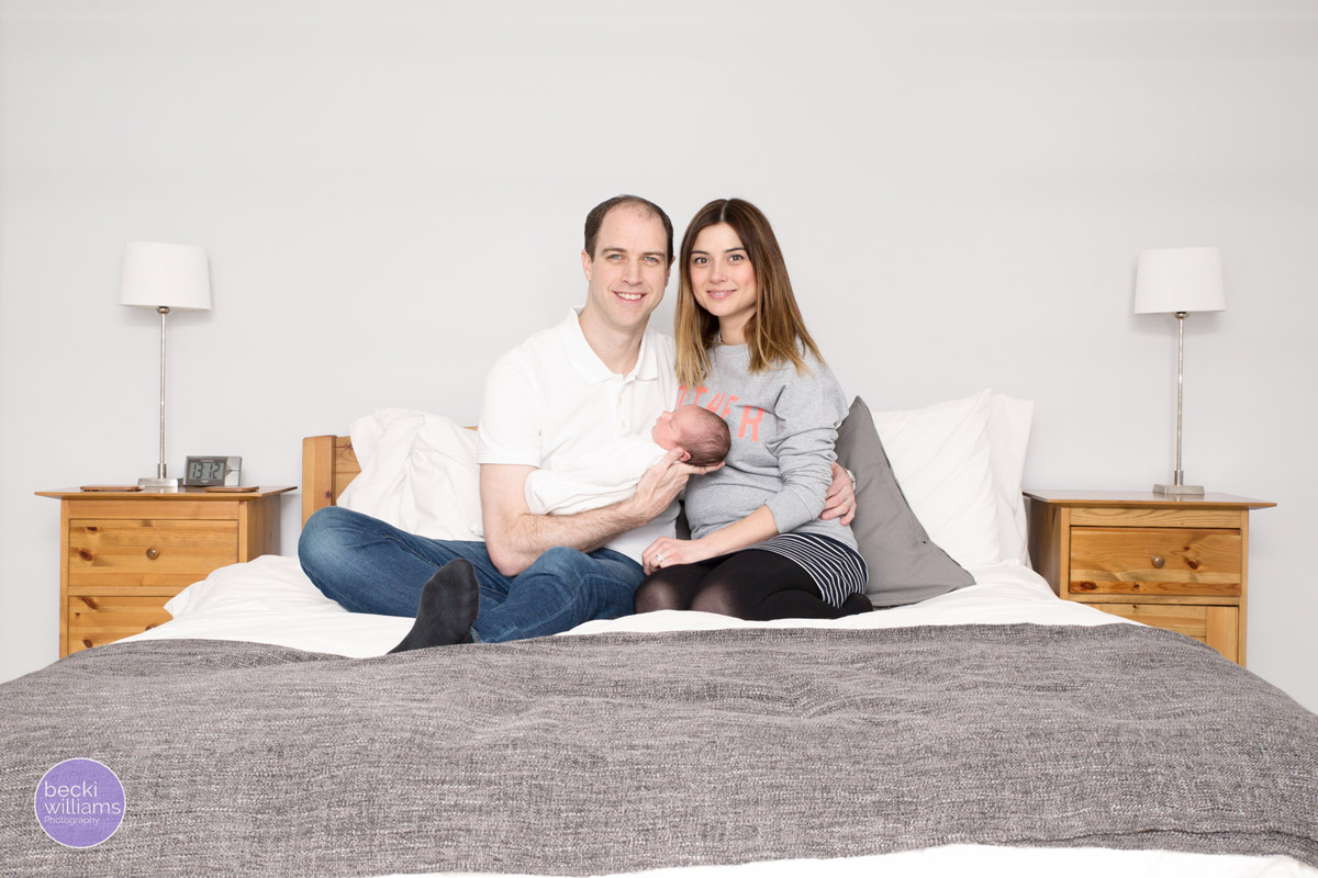 family with newborn cuddling on a bed