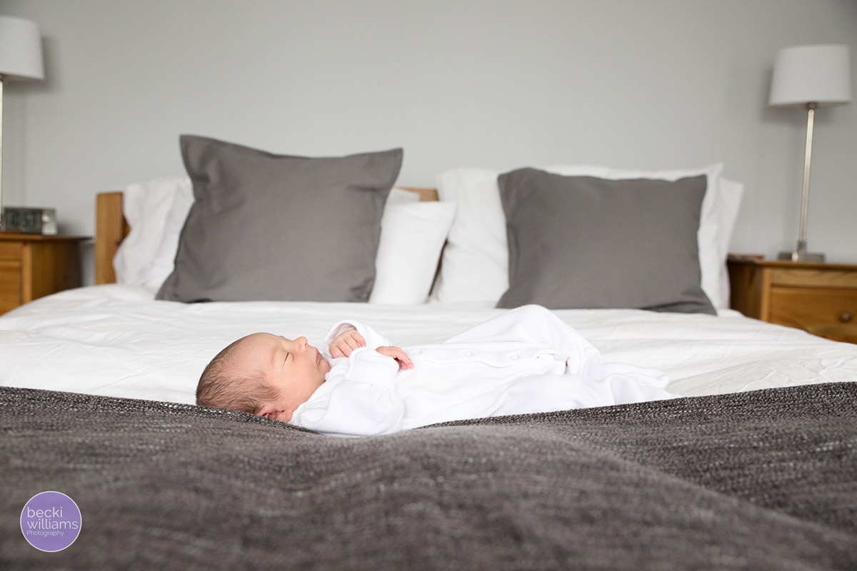 newborn baby laying on a bed