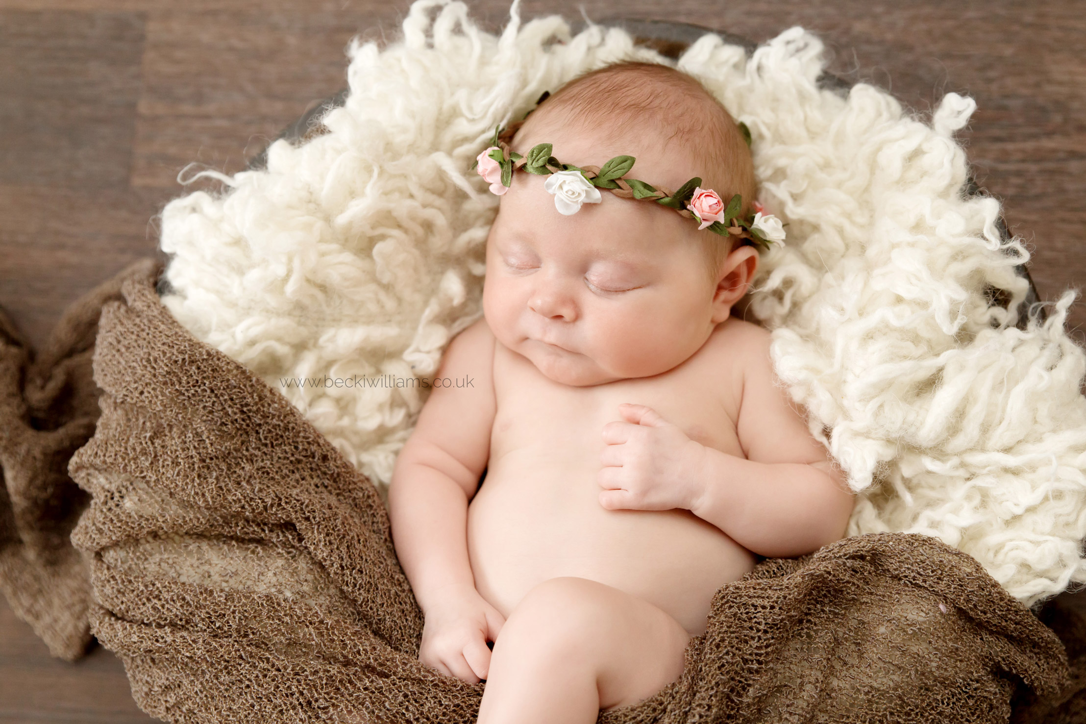 Newborn girl in wooden bowl with a flower headband