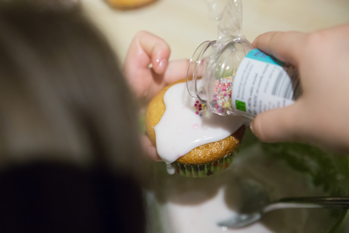 Little girl adds sprinkles to an iced cupcake.