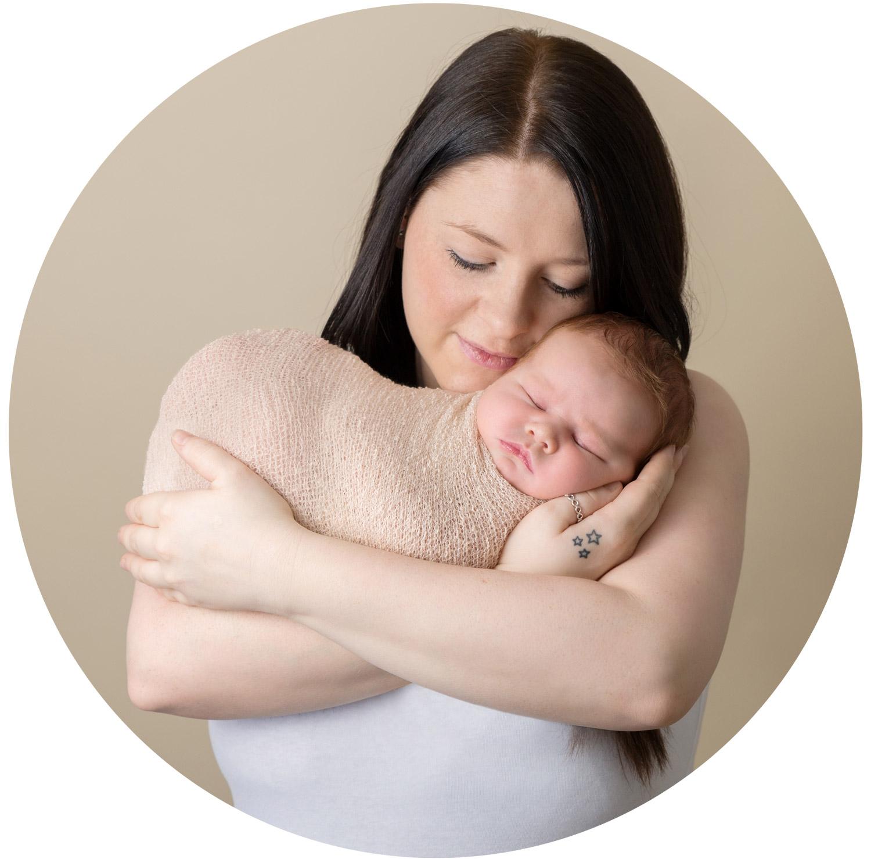 New mum holding her newborn baby for posed newborn photo shoot in hemel hempstead