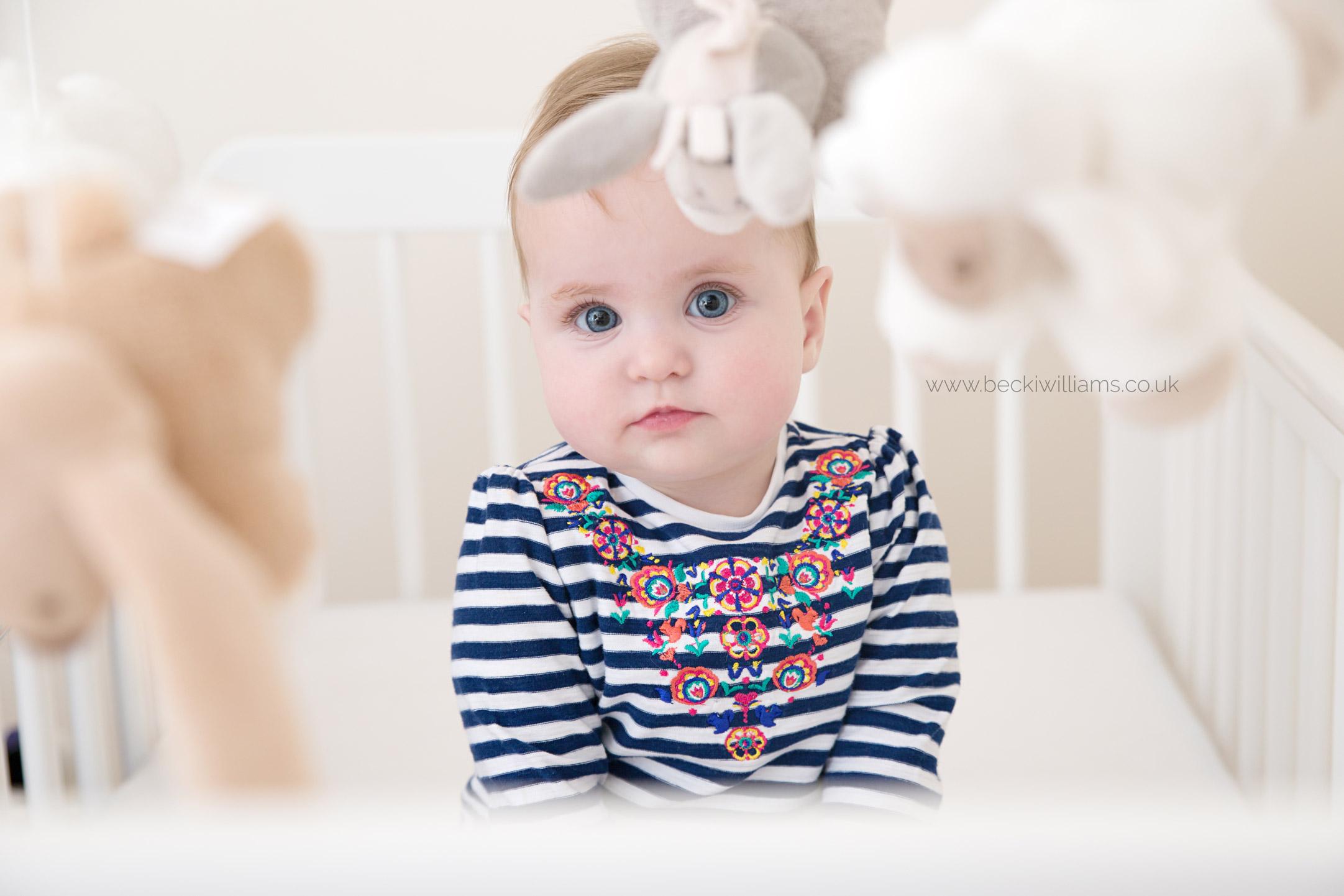 Baby-photography-hemel-hempstead-baby-in-cot-through-mobile