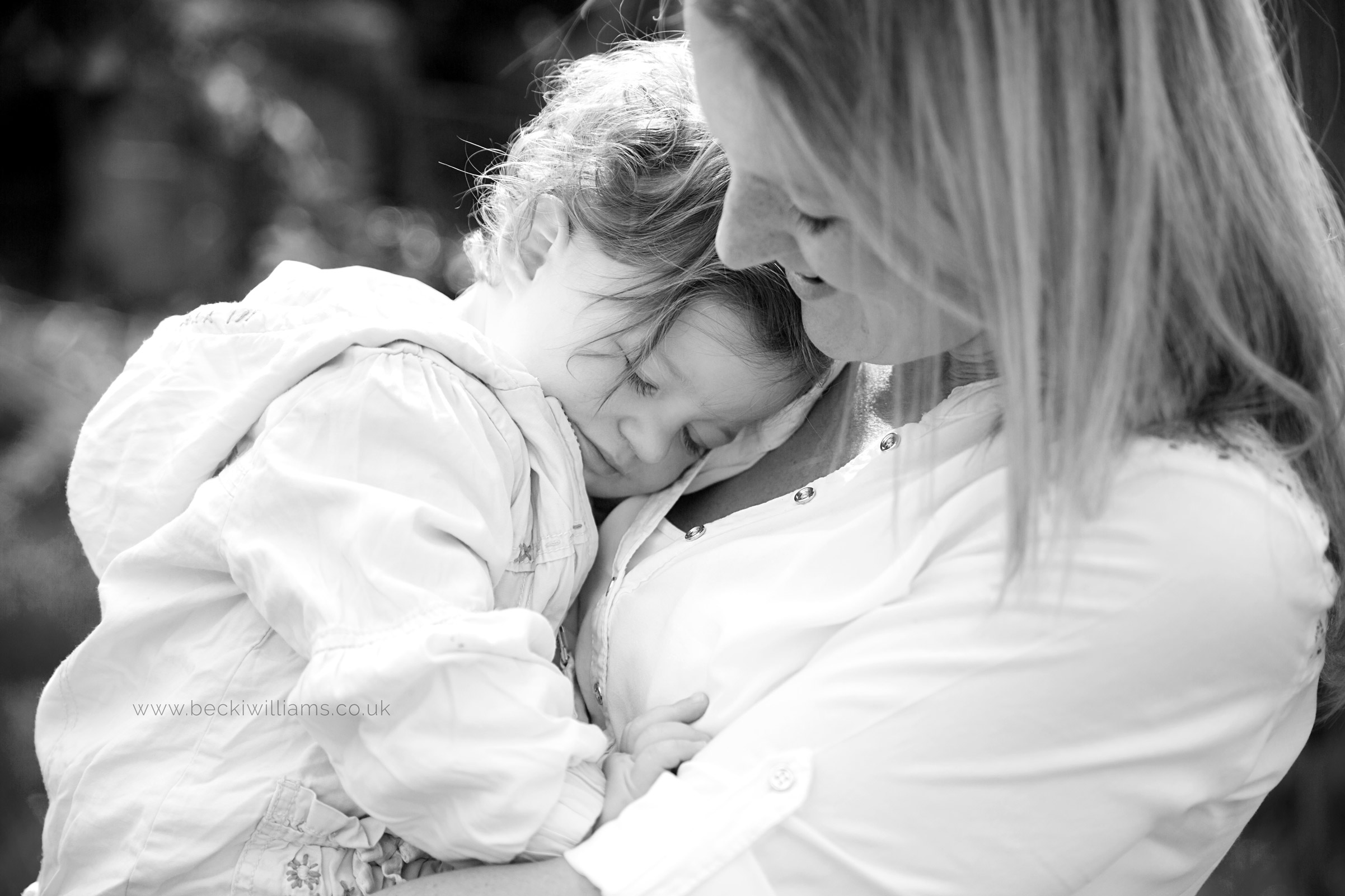 1 year old cuddles mum in the garden for photo shoot