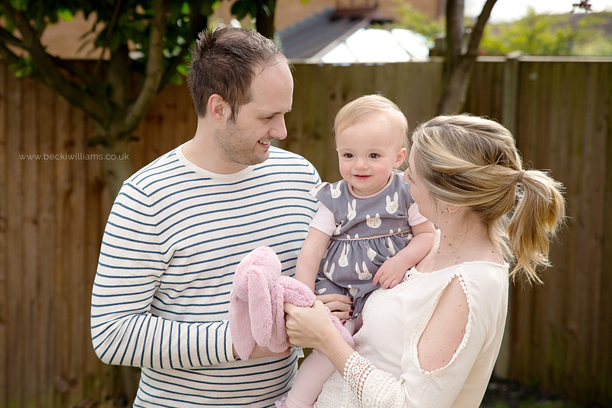 family cuddles with a 1 year old in the garden in luton. Hemel Hempstead photography