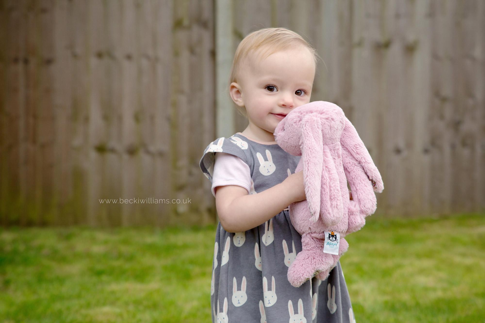 1 year old cuddles pink bunny in the garden. hemel hempstead photography