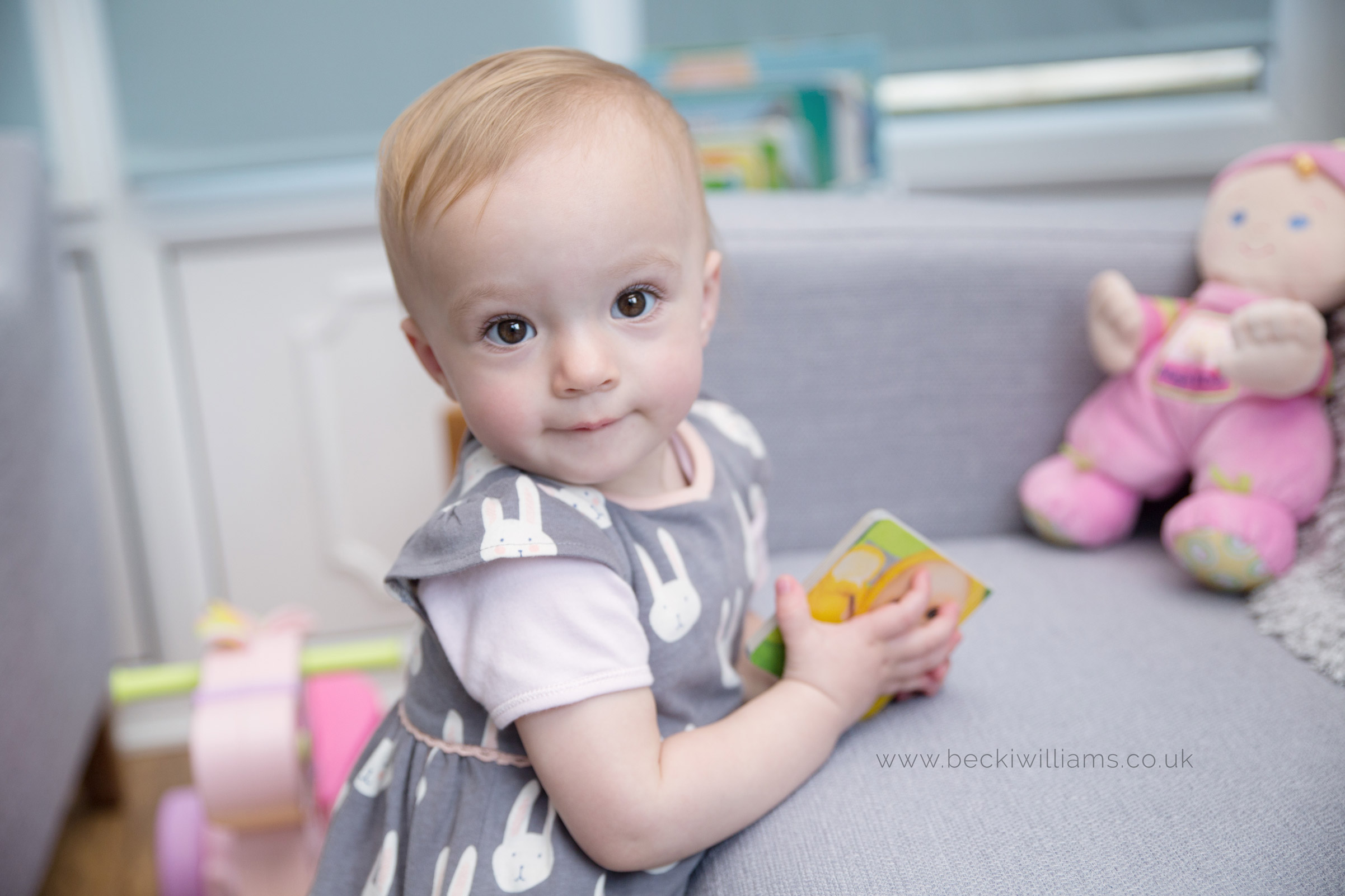 1 year old leans on sofa for photography shoot