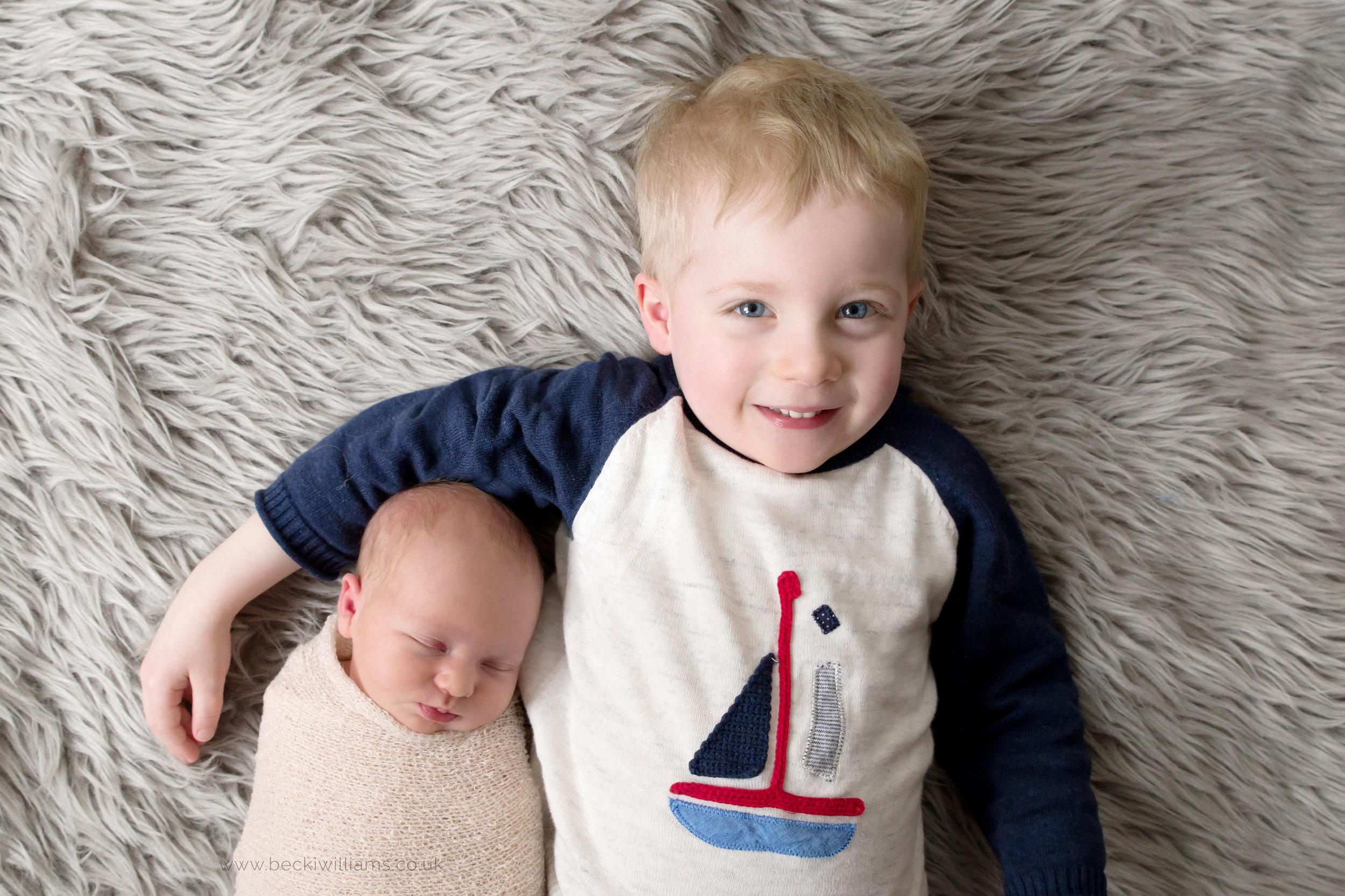 Newborn girl sleeps at photo shoot with big brother