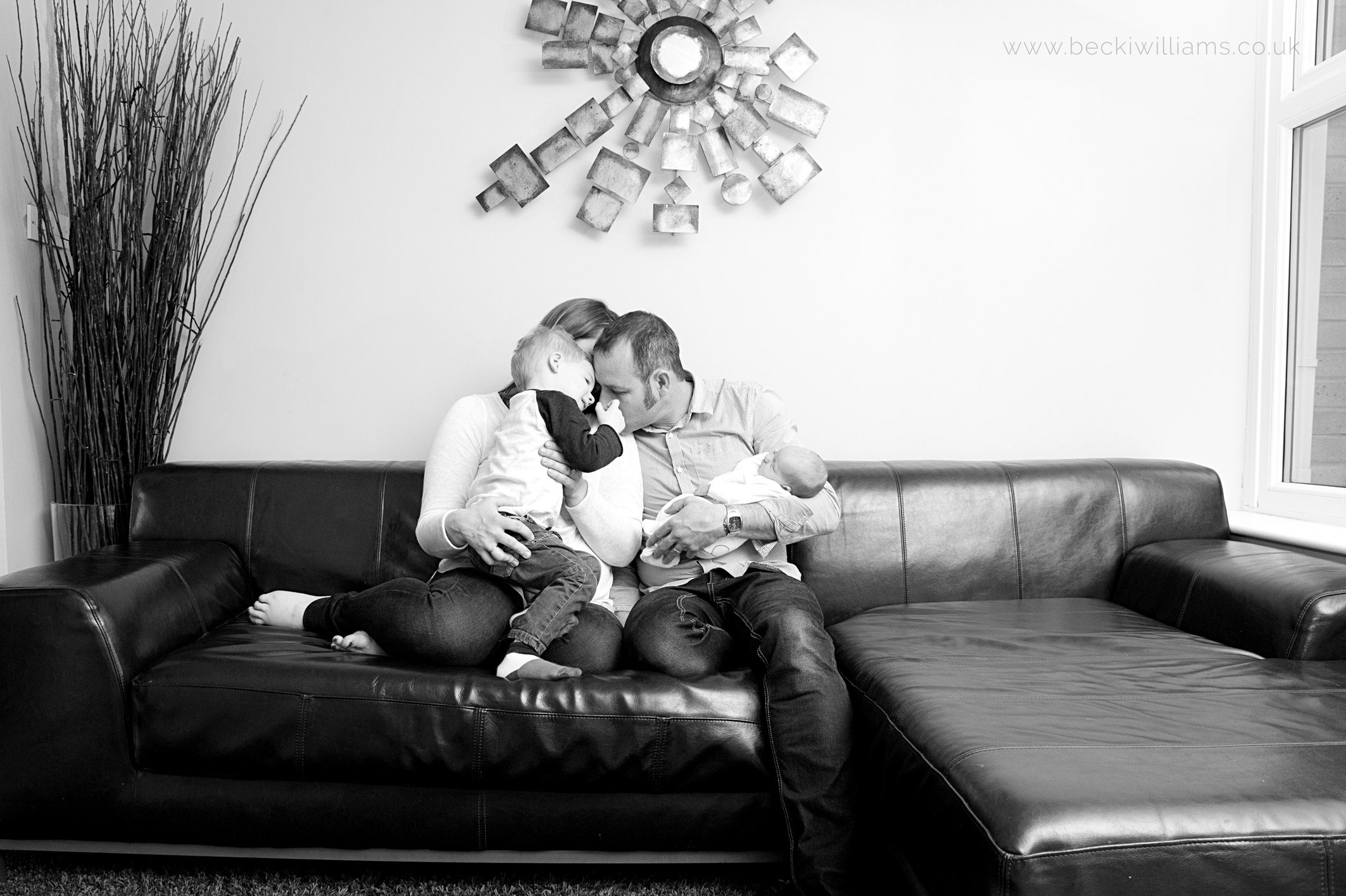 Family with newborn baby at professional photo shoot