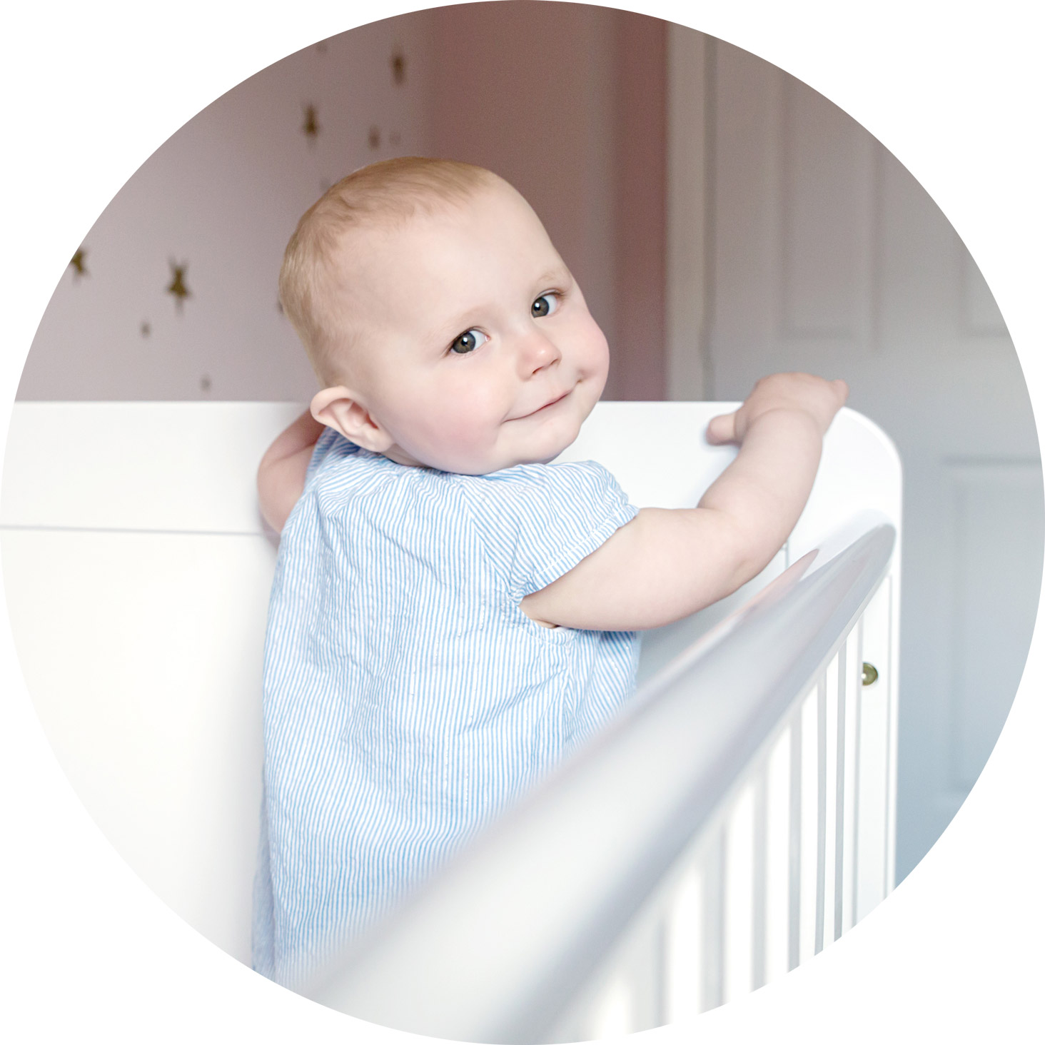 professional baby photography in hemel hempstead - 1 year old smiling in her cot