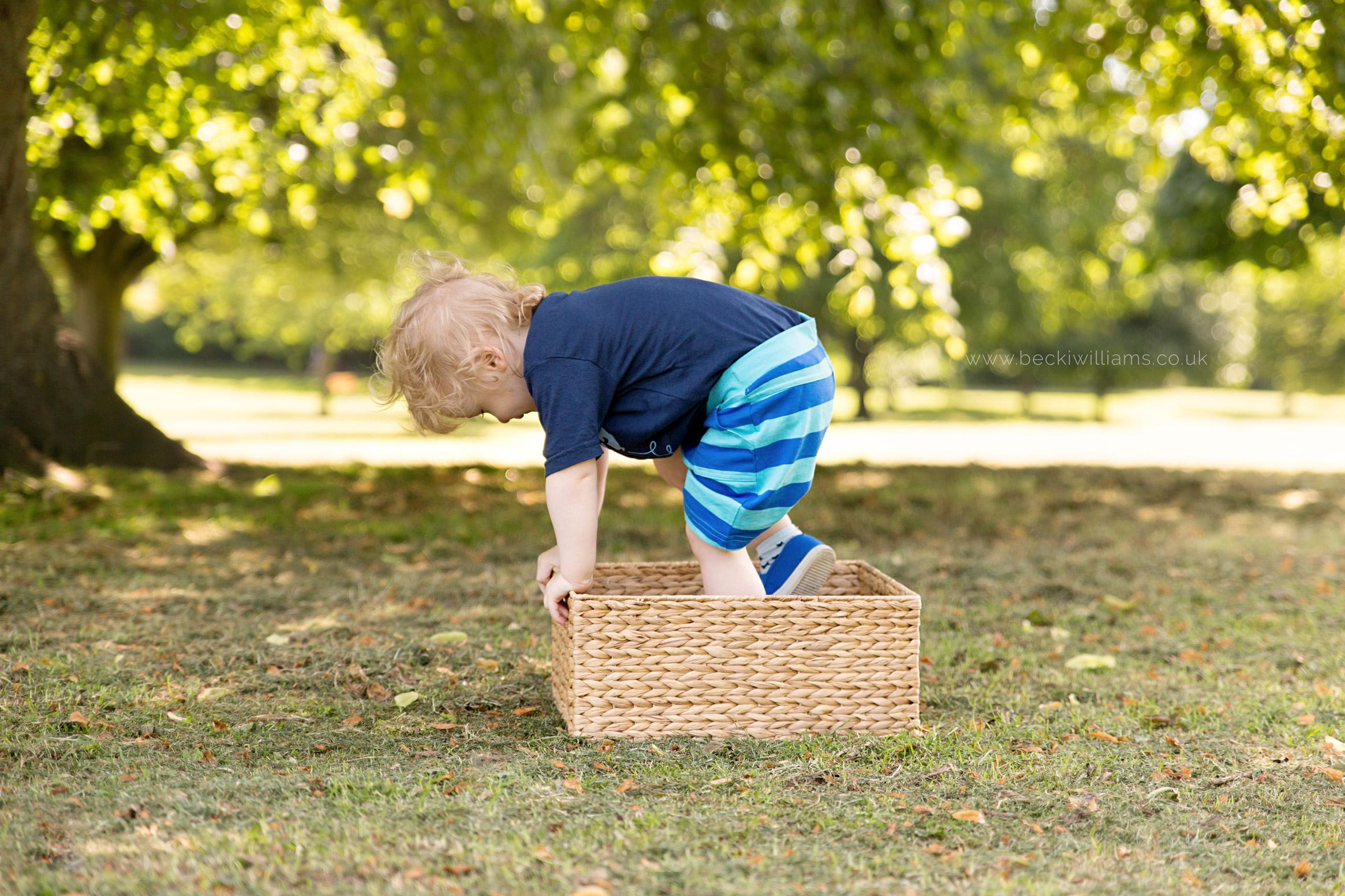 professional baby photography of 2 year old boy playing in a box in gadebridge park, hemel hempstead