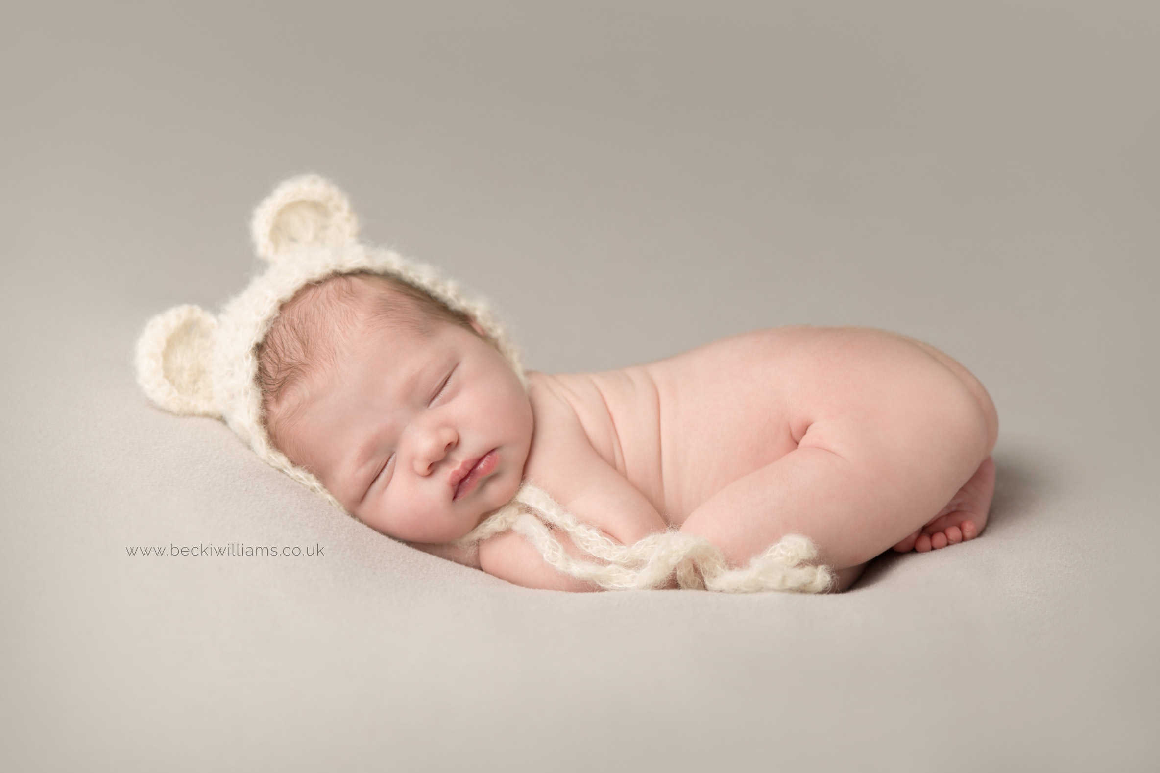 professional photo shoot of newborn baby in hemel hempstead. baby laying on it's tummy wearing a cute bear hat.