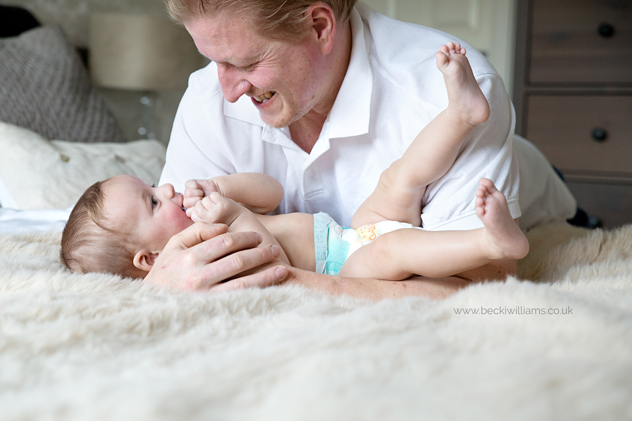 8 month old playing with dad on bed for professional photography in hitchin