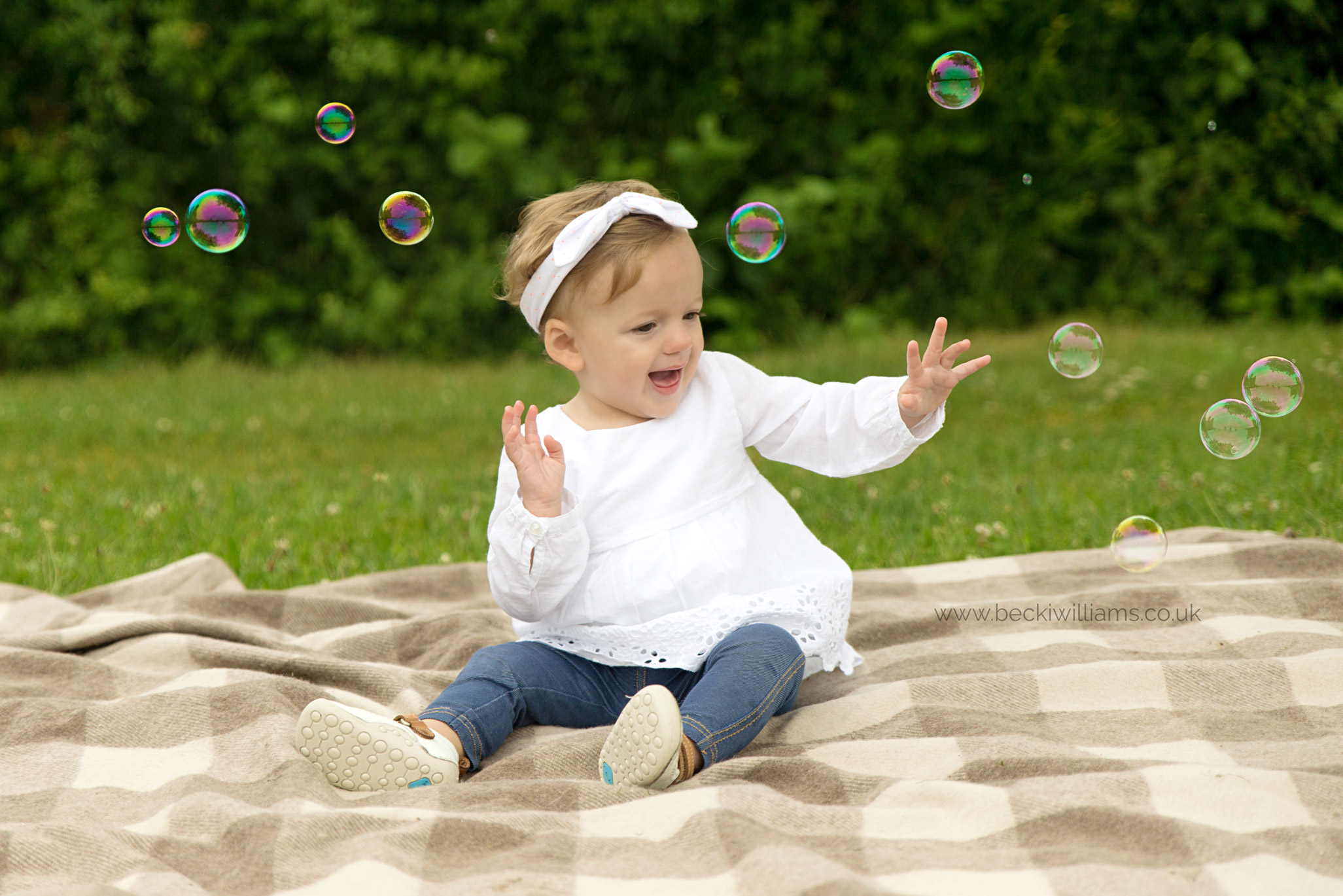 1 year old girl plays with bubbles in a park for photo shoot